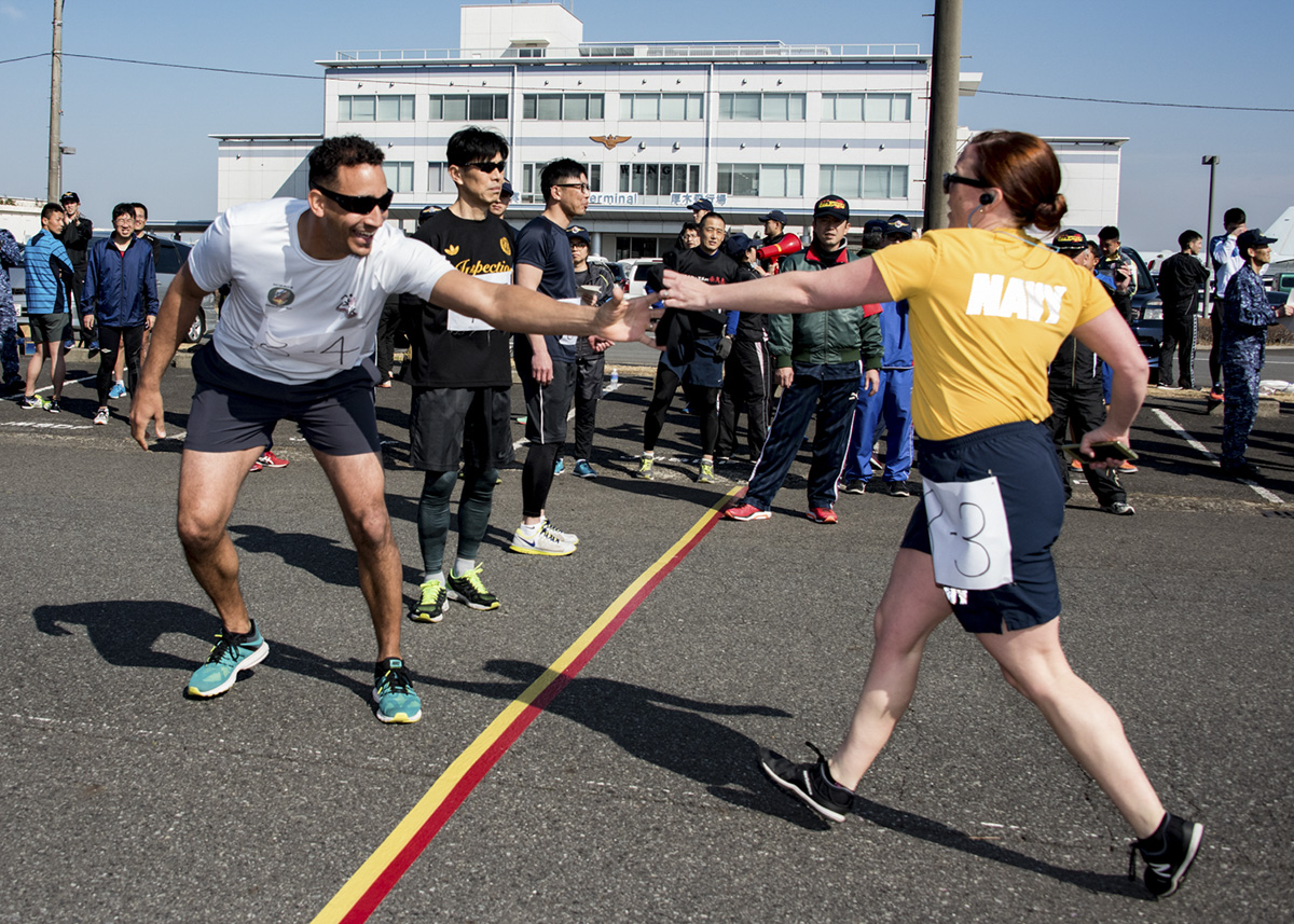 Chief Master-at-Arms Adam Turner, left, from Floyd, Va., takes the runner sash from Chief Air Traffic Controller Stephanie Breault, from Dracut, Mass., during the biennial Ekiden relay race at Naval Air Facility Atsugi. The Ekiden was hosted by Japan Maritime Self-Defense Force Air Patrol Squadron 3 to foster teamwork and cooperation between the various commands on the installation. (MC2 Matthew C. Duncker/Navy)