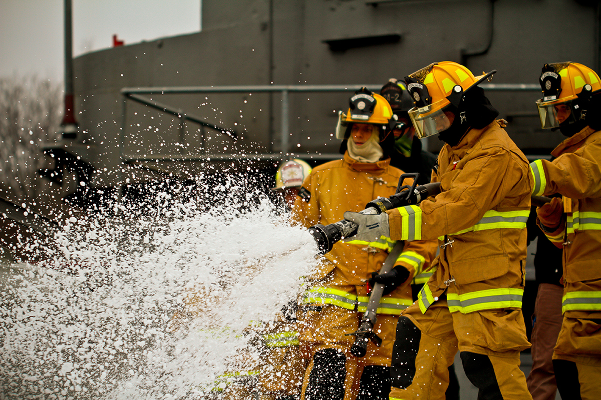 Air Force fire protection specialists douse a simulated ship fire with foam during a training exercise at the Military Sealift Command Training Center East in Freehold, N.J., on Dec. 5, 2013. (Tech. Sgt. Matt Hecht/Air National Guard)