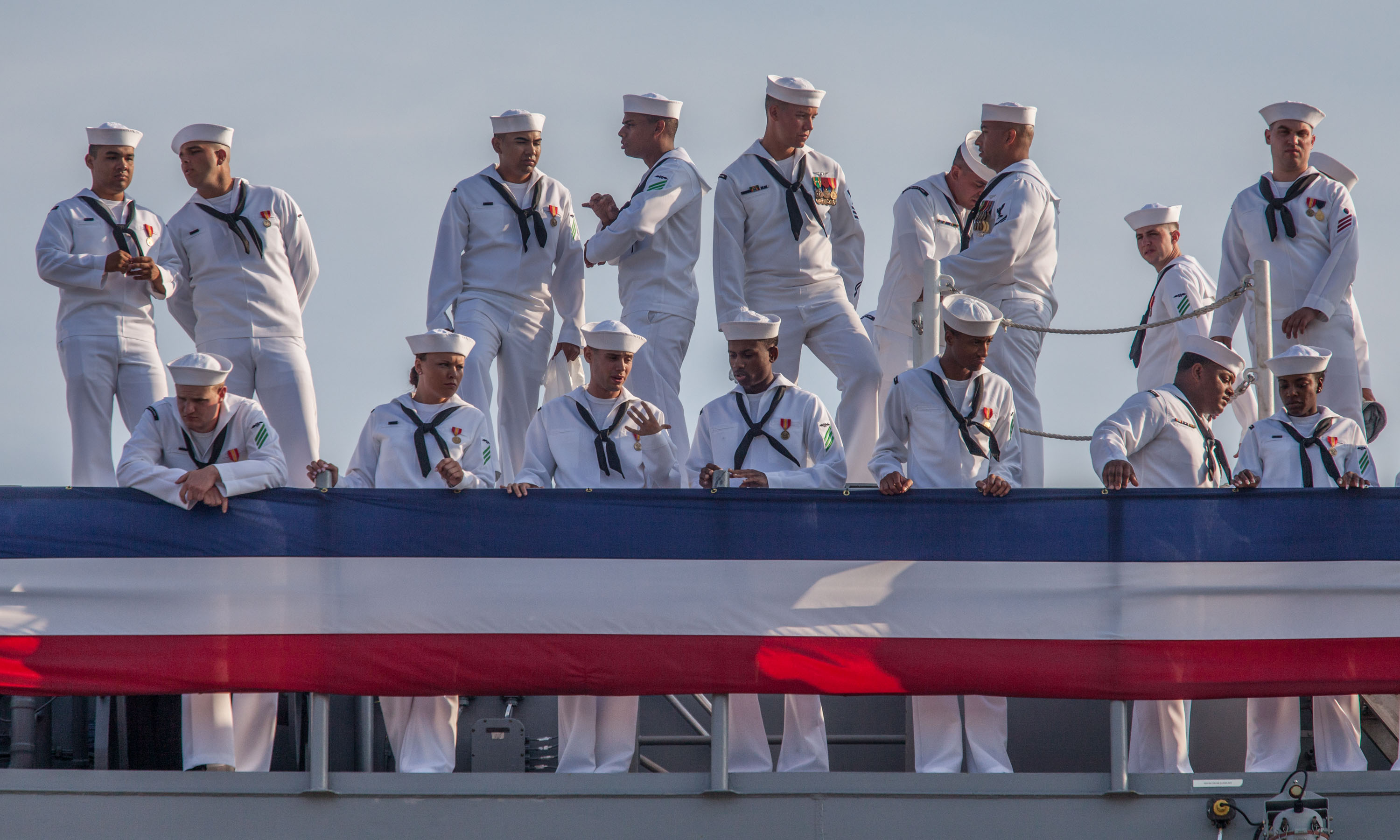 Sailors aboard the aircraft carrier Gerald R. Ford watch as the crowd gathers on pier II to watch their ship join the fleet today. The Ford is the first of a new class of carriers and won't be fully ready to deploy for another five years.