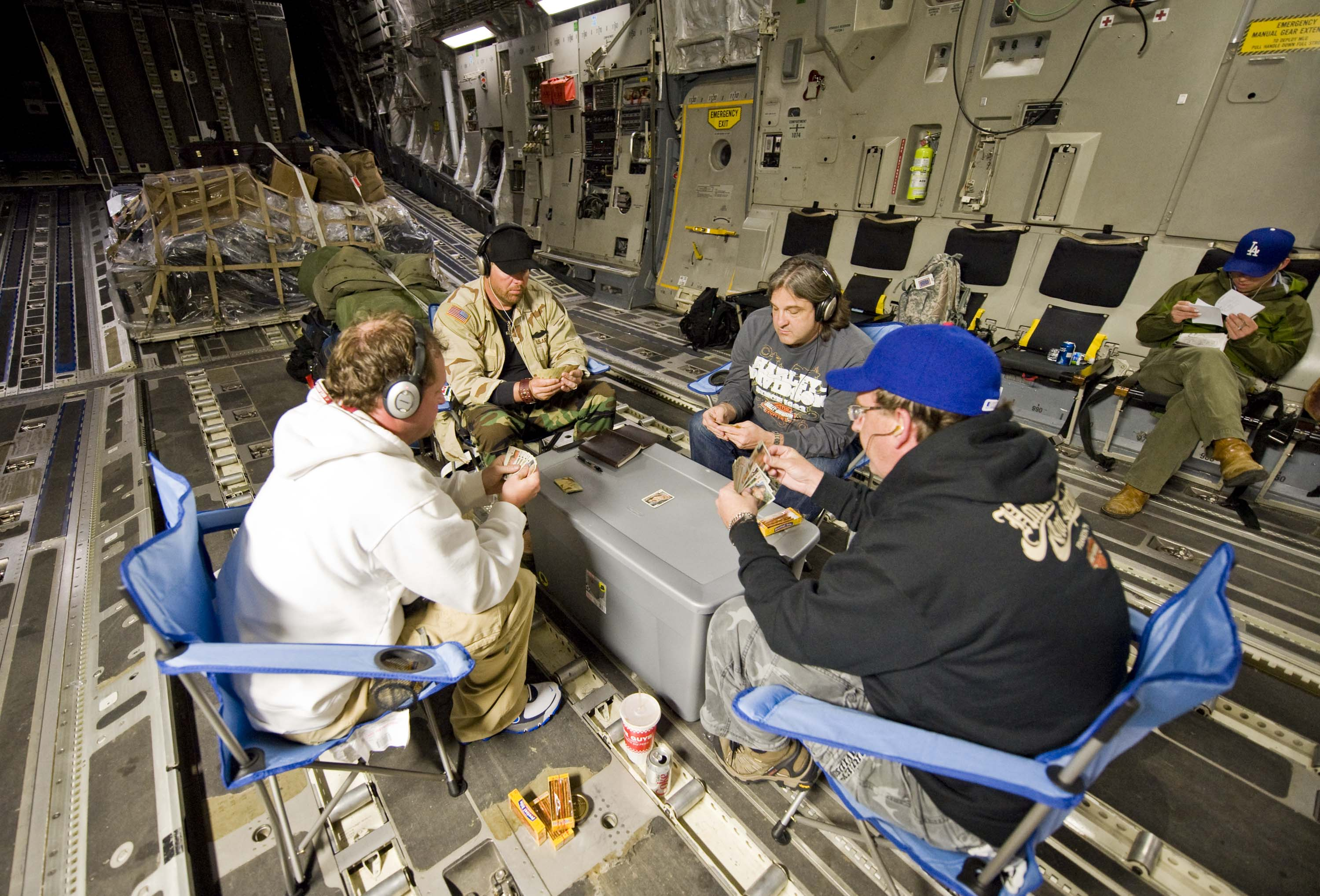 Toby Keith in Afghanistan in 2009 putting on shows at Forward Operating Bases, most of which haven't had any outside entertainment in six months. The core group with Toby Keith (C-black hat) play their traditional game of Spades off folding chairs and a storage box, at the rear of the C-17 on the flight to Germany for refueling and maintenance. (L-R) Brian O'Connell, Toby, Curt Motley, and Mitch DeNeui (back to camera). (Dave Gatley/USO)