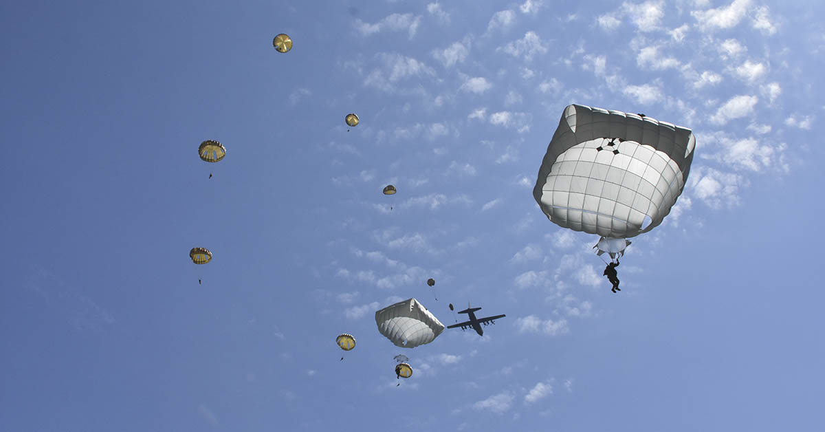 Parachutes from France, Holland, Germany, Romania and the United States descend on to Iron Mike Drop Zone near Sainte Mere Eglise, France where paratroopers jumped into World War II 74 years ago. (Lt. Col. John Hall/Army)