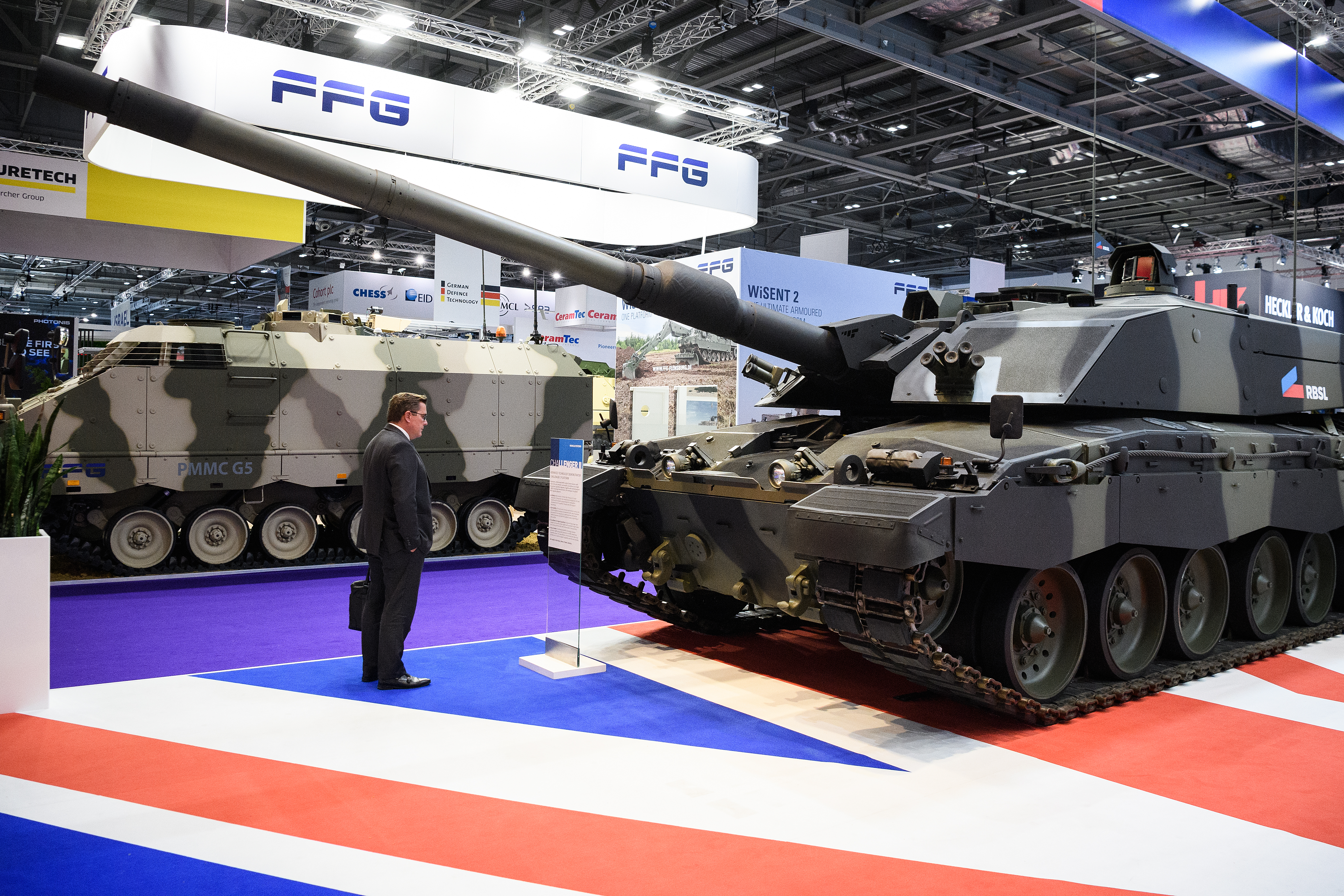 A delegate studies a Challenger II tank at DSEI. In London's Doclands area, the biennial event is the world's largest arms fair. (Leon Neal/Getty Images)