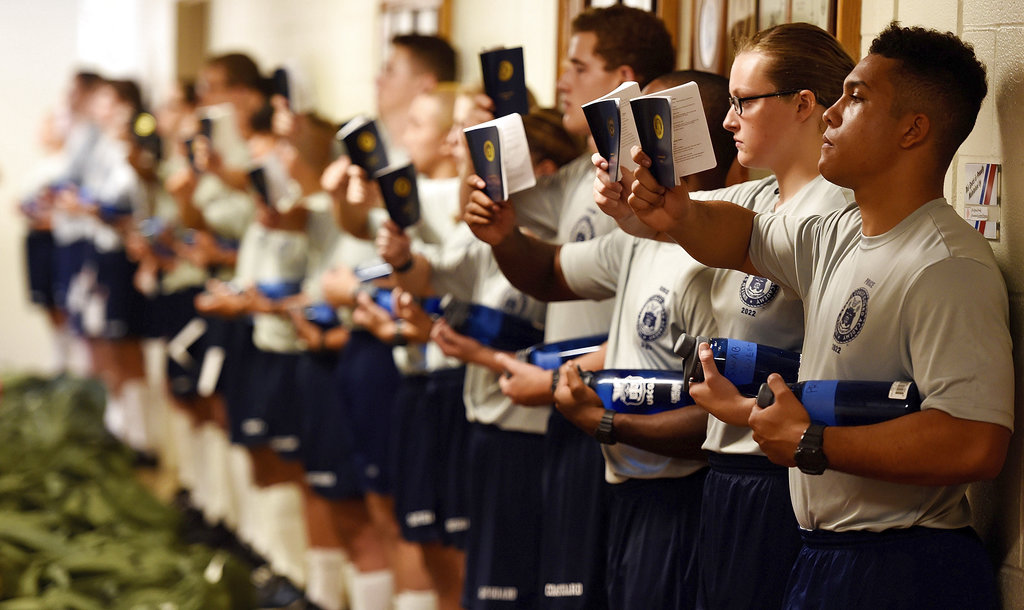 Swabs of Whiskey One company read their Running Light guidebooks as they wait to be issued their uniforms on Day 1 for the U.S. Coast Guard Academy Class of 2022 on July 2, 2018 at the academy in New London, Conn. (Sean D. Elliot/The Day via AP)