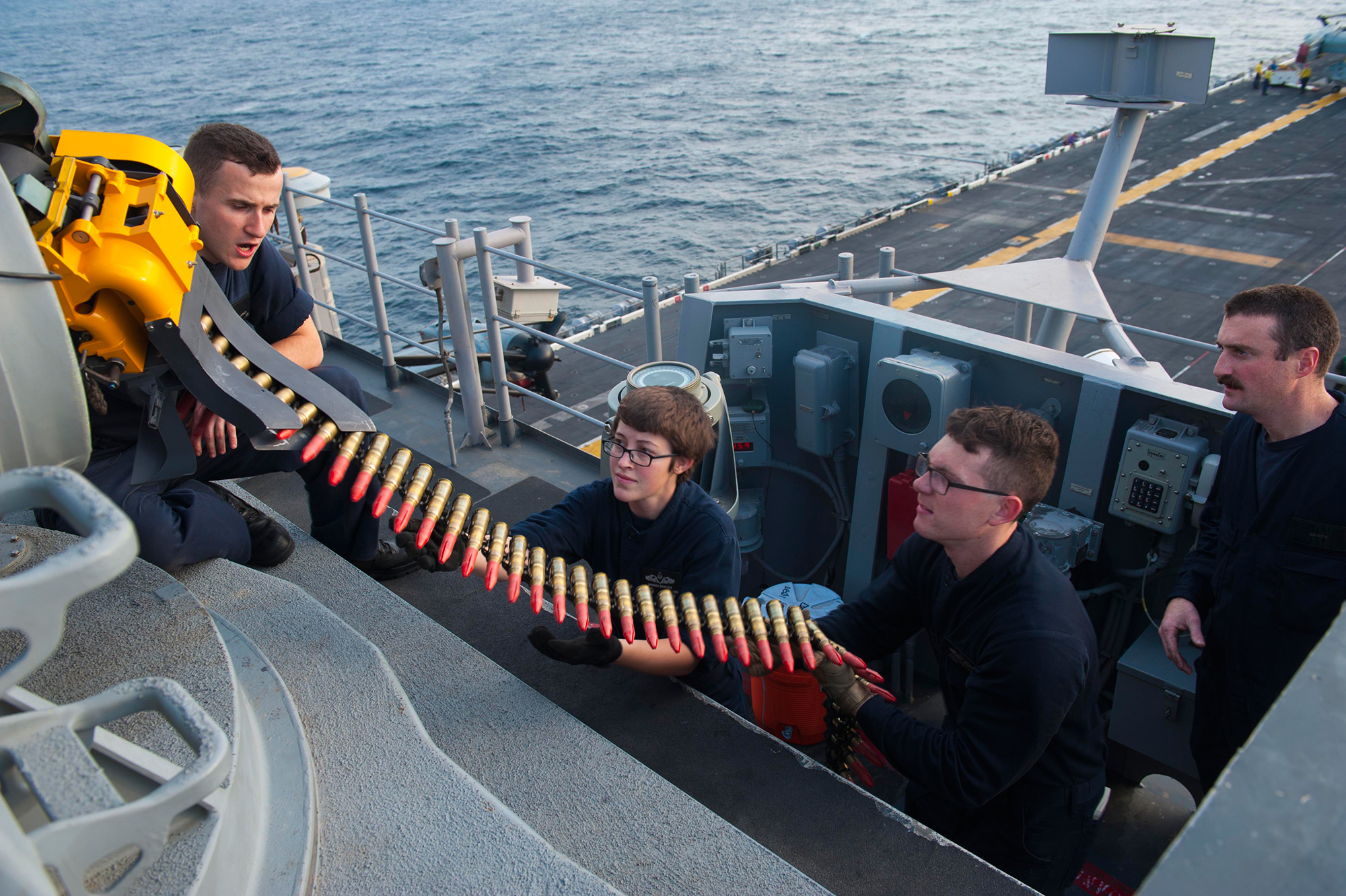 Sailors assigned to the command, control, communications, computers, collaboration and intelligence department aboard the amphibious assault ship USS America (LHA 6) load the forward closed-in weapons system with 20mm rounds in preparation for a live exercise on Dec. 20, 2017, in the Indian Ocean. (Mass Communication Specialist Seaman Daniel Pastor/Navy)