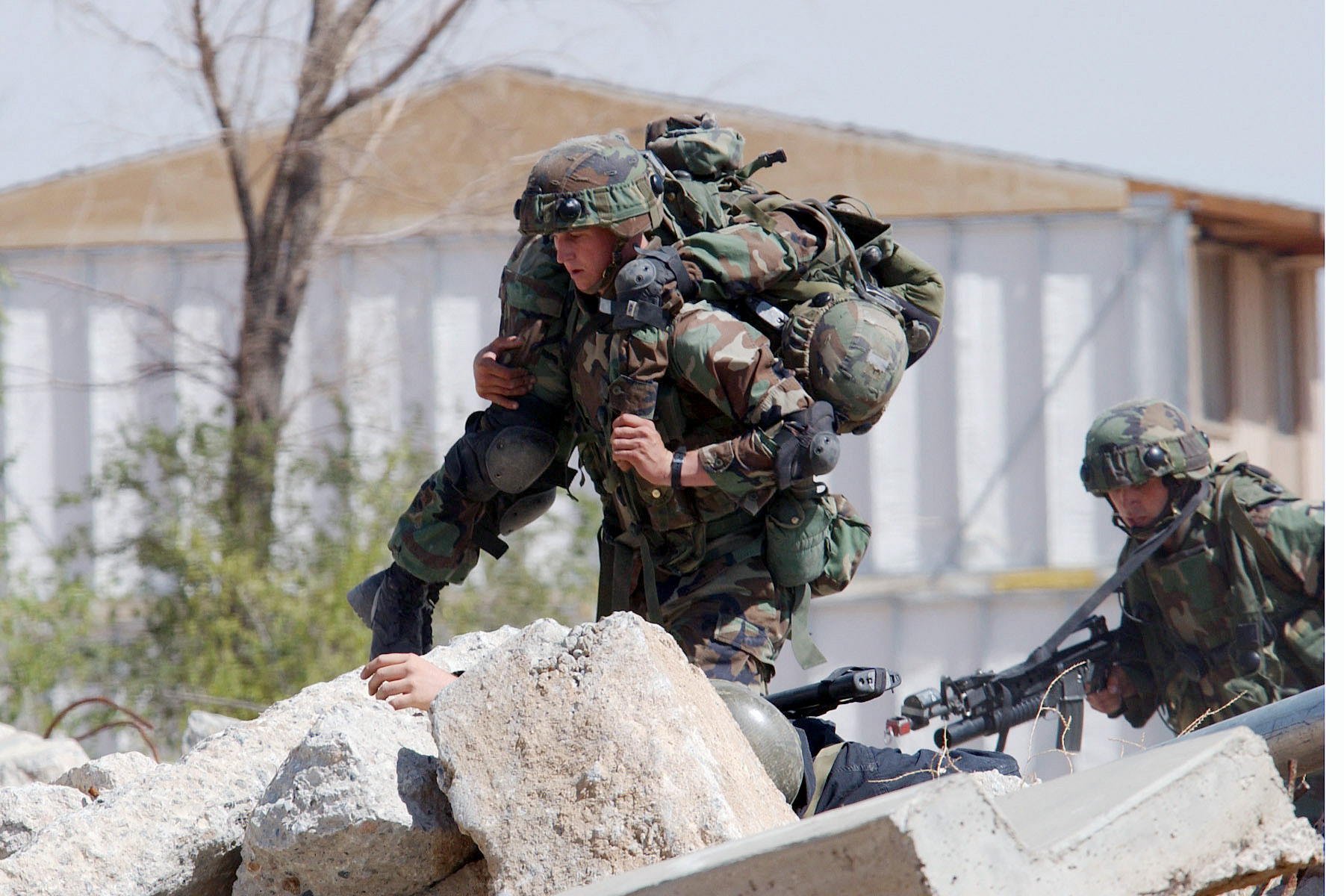 A Marine carries a wounded comrade to safety during an urban combat training demonstration being conducted at the Southern California Logistics Airport, formerly George Air Force Base, during the joint service experimentation process dubbed Millennium Challenge 2002. While the base was closed, the military continued to use it for training exercises. (RDO).
