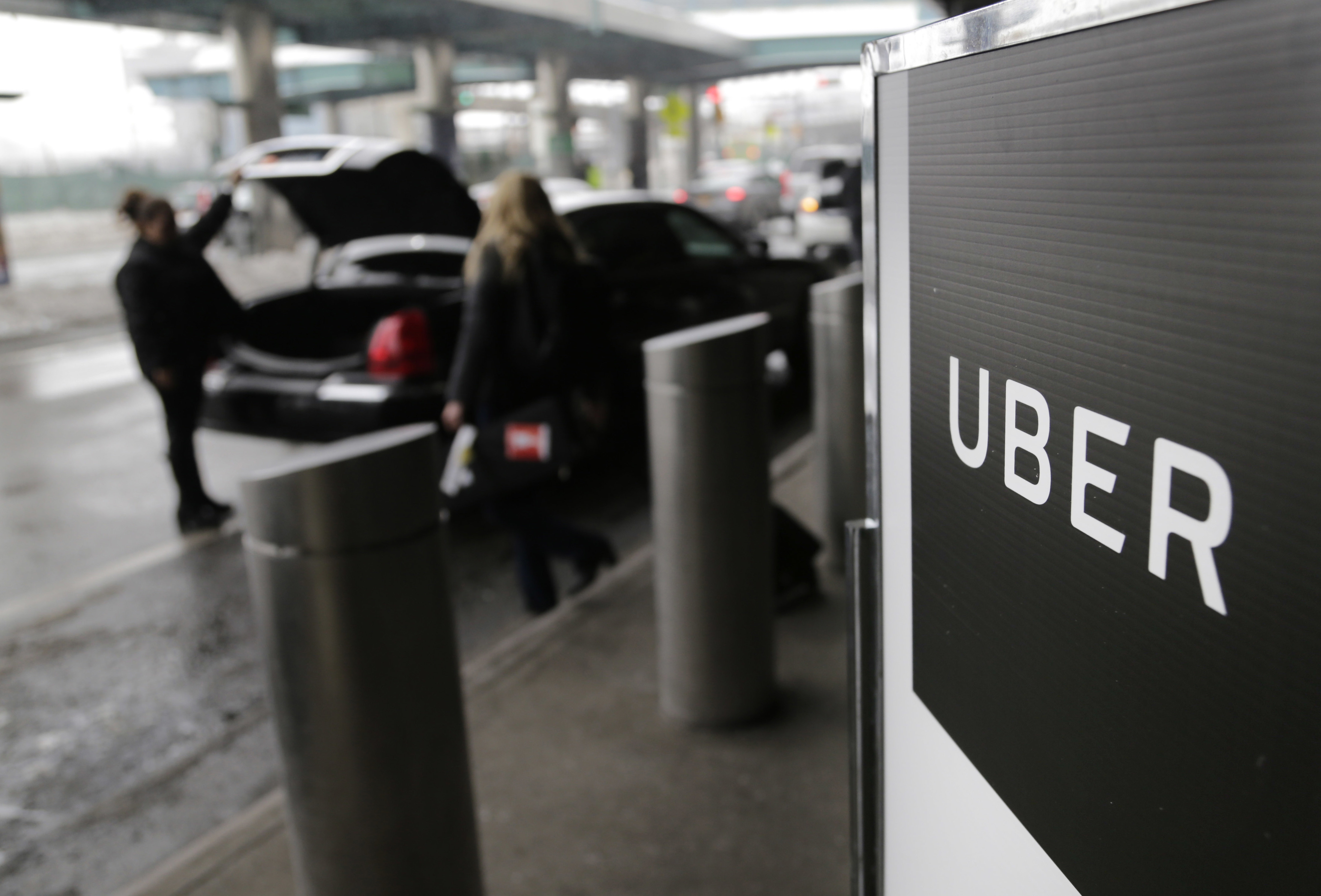 In this March 15, 2017, file photo, a sign marks a pick-up point for the Uber car service at LaGuardia Airport in New York. (Seth Wenig/AP)