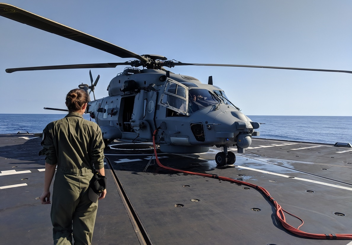 A member of the aircrew walks across the flight deck to prepare for an afternoon flight in the Alpino's NH90 helicopter. (David B. Larter/Staff)