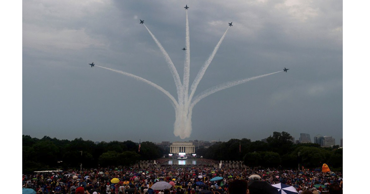 The U.S. Navy Blue Angels fly overhead as people gather on the National Mall for the