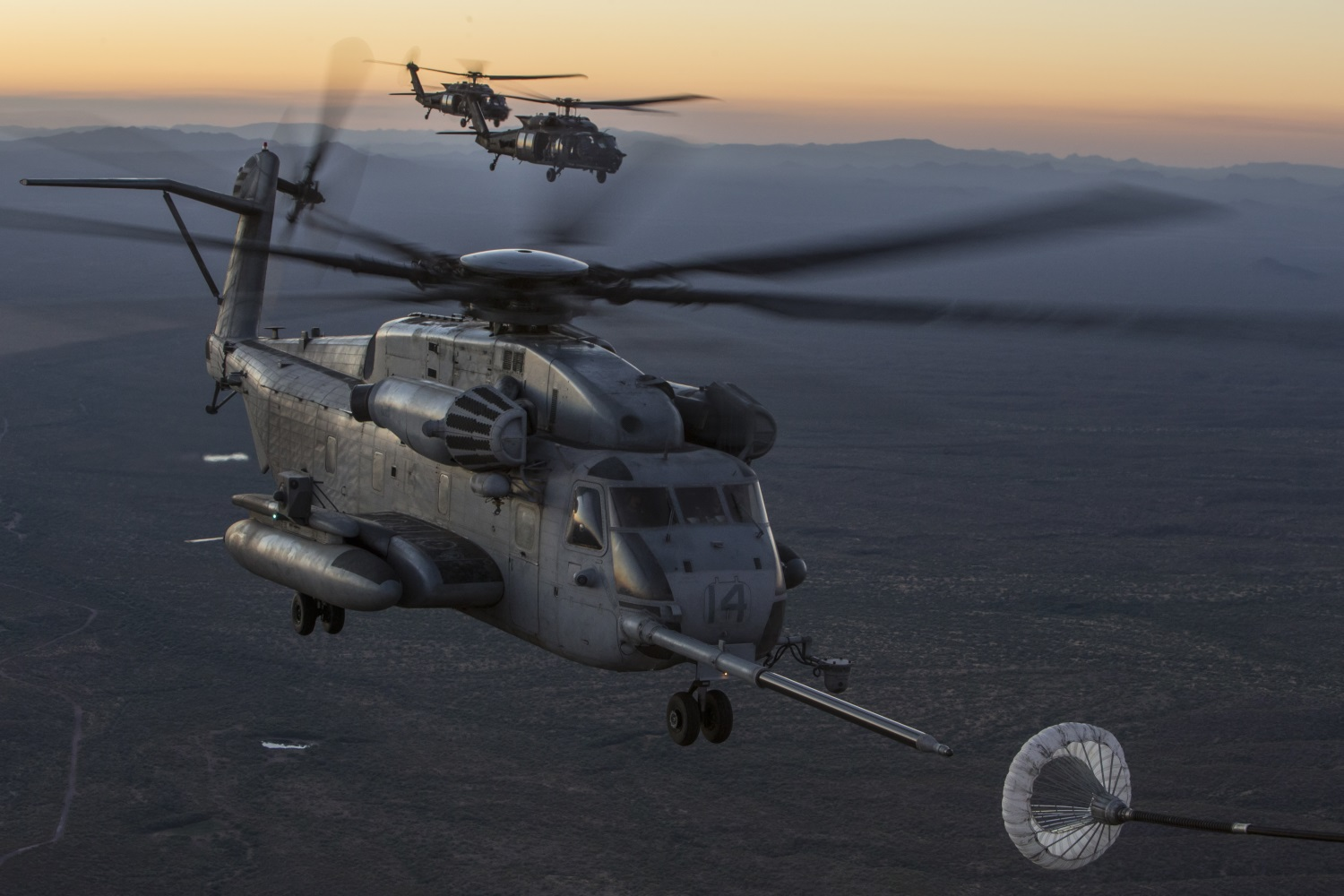 A U.S. Marine Corps CH-53E Super Stallion and U.S. Army MH-60M Black Hawks assigned to Marine Corps Aviation Weapons and Tactics Squadron One (MAWTS-1) conduct an aerial refueling exercise in support of Weapons and Tactics Instructor course (WTI) 1-18 in Yuma, Ariz., Oct. 6, 2017. (Sgt. Allison Lotz/Marine Corps)