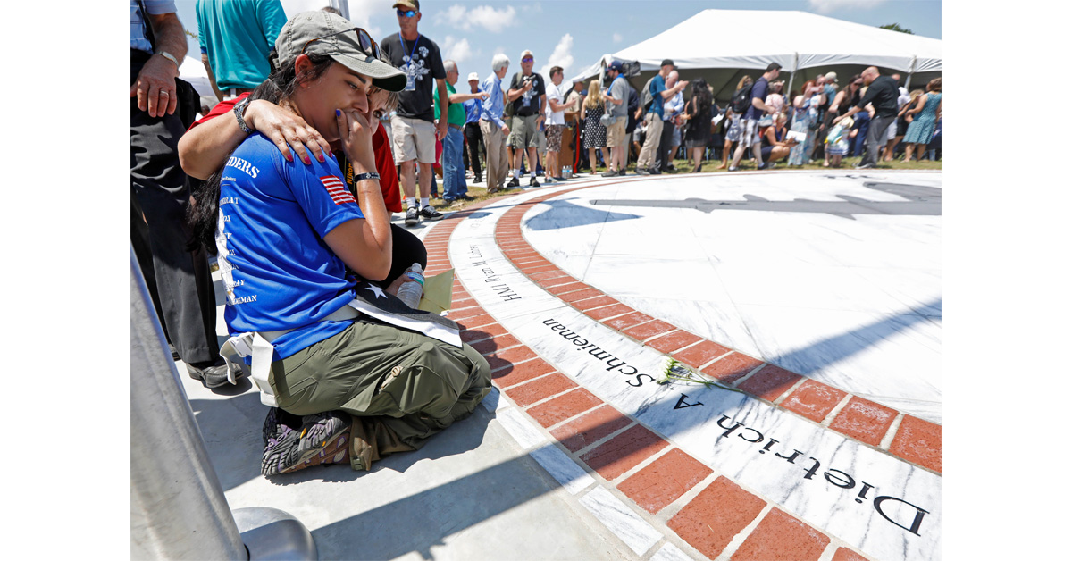 Morgan Zoufal is comforted as she reacts to seeing the name of her late fiancee, Marine Sgt. Dietrich A. Schmieman, on a marble monument honoring the 15 Marines and one Navy corpsman who died in a 2017 plane crash near Itta Bena, Mississippi. (Rogelio V. Solis/AP)