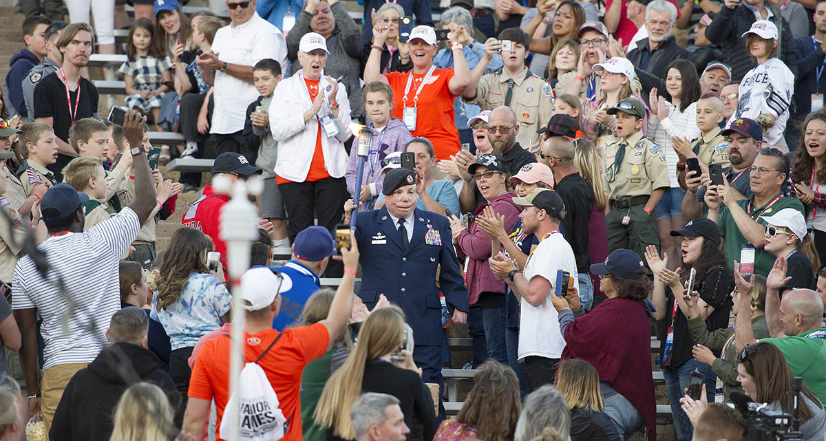 Senior Master Sgt. Israel Del Torro, first torch barrier for the DoD Warrior Games, walks through the crowd inside Falcon Stadium carrying the torch during the opening ceremonies of this years Warrior Games, June 2, 2018. The Warrior Games, taking place June 1-9, 2018, at the U.S. Air Force Academy in Colorado, are Paralympic-style competition for wounded, and injured service members from all U.S. branches of service and this year include teams from the United Kingdom Armed Forces, Australian Defence Force and Canadian Armed Forces. (Master Sgt. Stephen D. Schester/DoD)