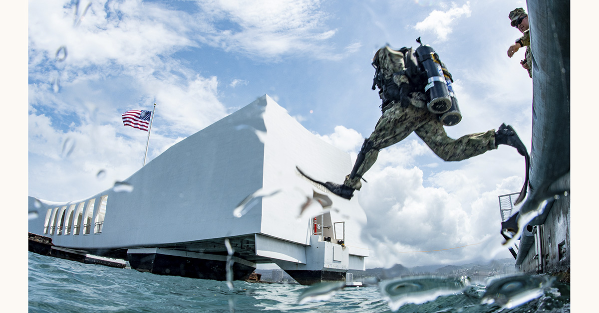 Builder 2nd Class Aaron Brown, assigned to Underwater Construction Team (UTC) 2, enters the water for a dive on the USS Arizona Memorial at Joint Base Pearl Harbor-Hickam during the Rim of the Pacific (RIMPAC) exercise, July 13, 2018. (MC1 Arthurgwain L. Marquez/Navy)