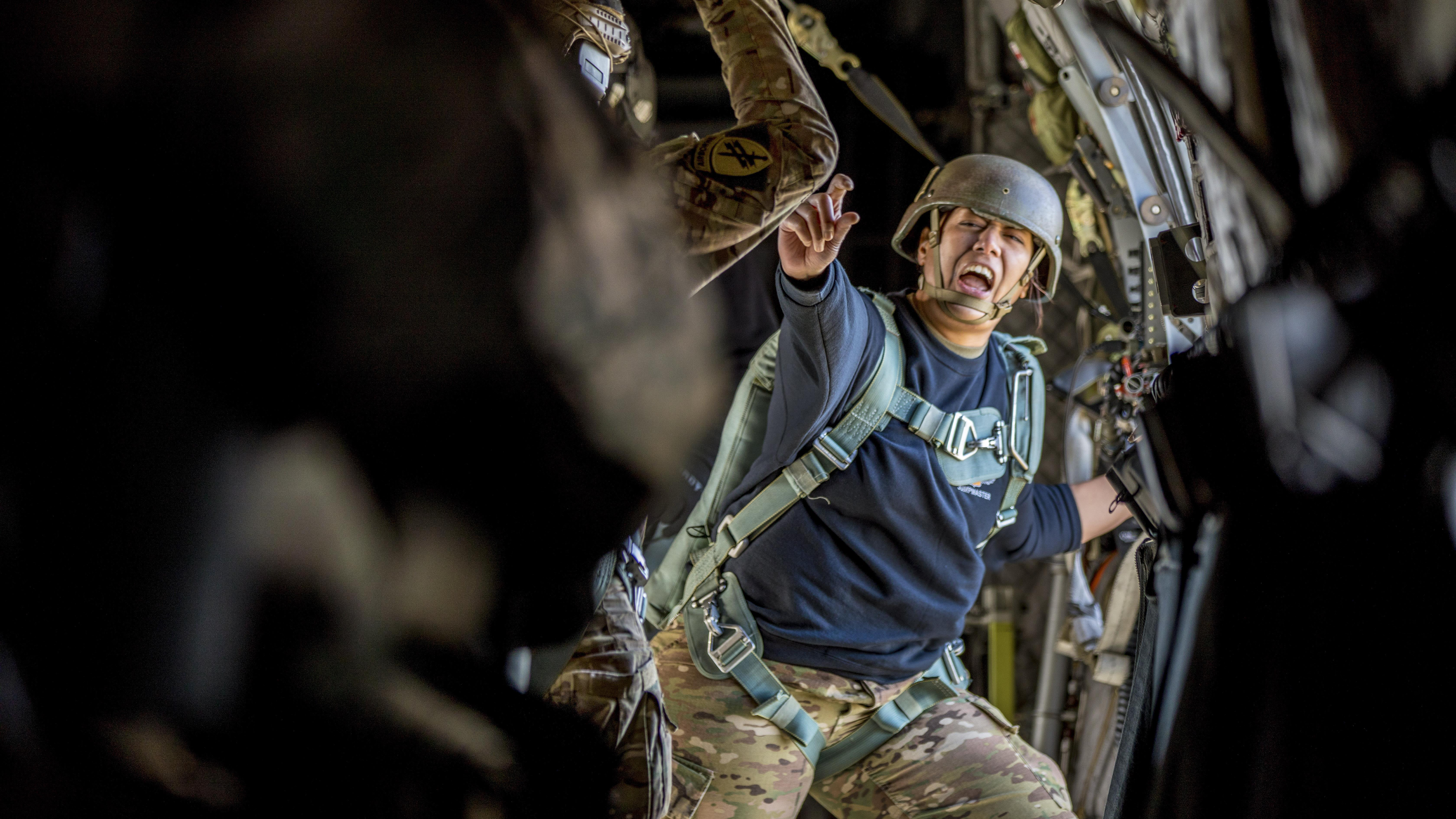 Army Staff Sgt. Nikita Revilloza, a jumpmaster, relays commands during the 20th Annual Randy Oler Memorial Operation Toy Drop at Camp MacKall, N.C. The event allows soldiers to maintain their airborne readiness and give back to the community. (Spc. Darius Davis/Army)