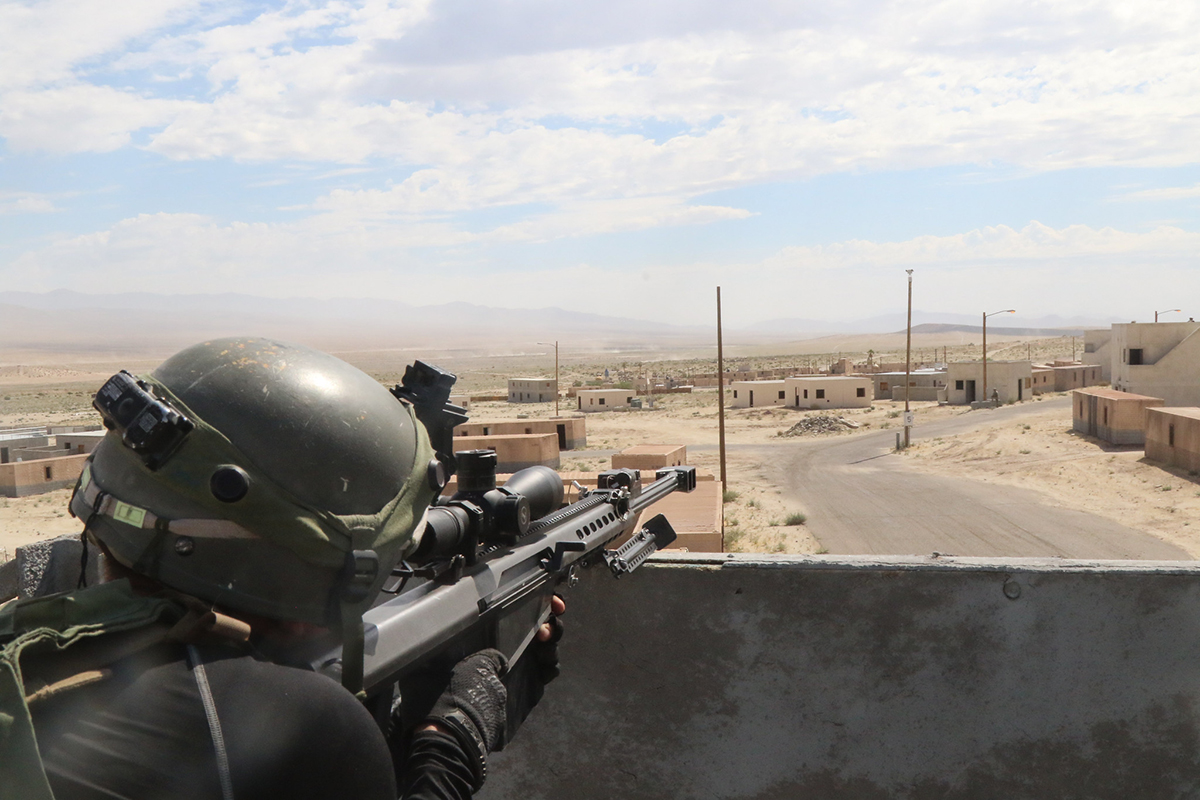A soldier surveys the battlefield with a simulated Barrett M107 .50 caliber sniper rifle on July 12, 2019, in the city of Razish at the National Training Center at Fort Irwin, Calif. (Pvt. James Newsome/Army)