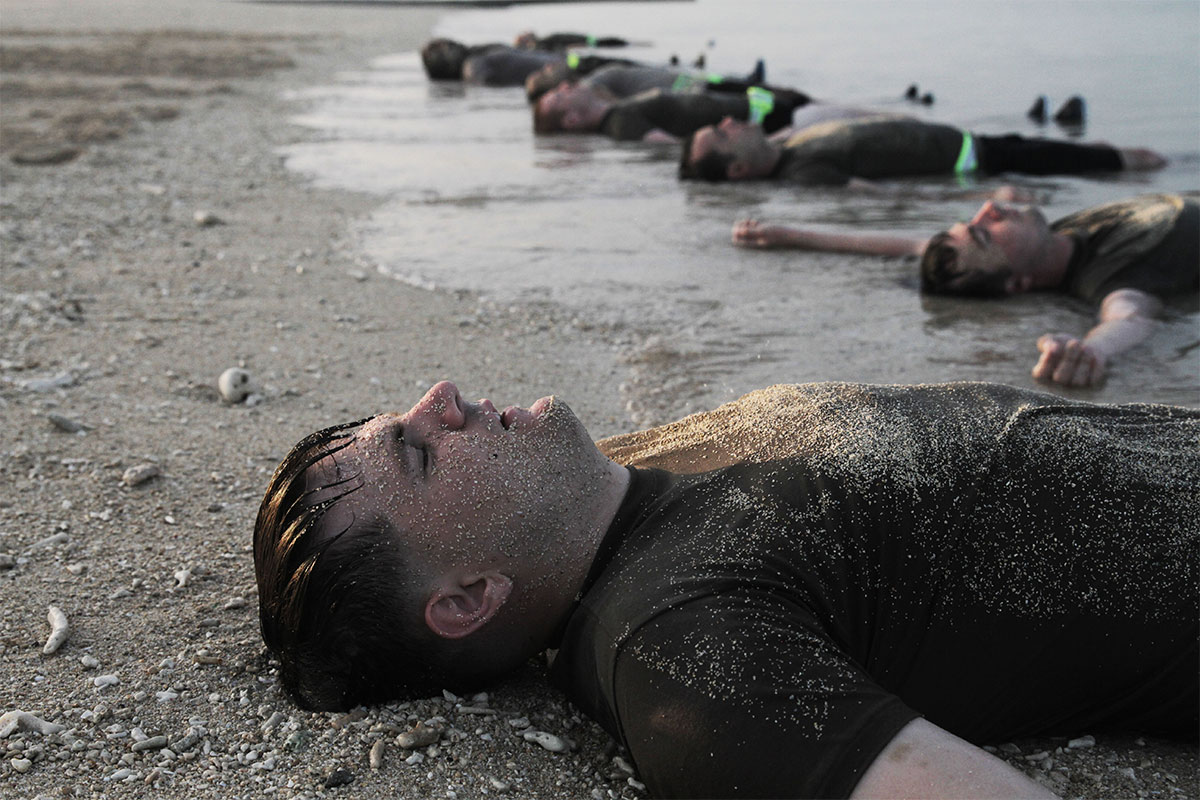 Soldiers from of the Special Forces Basic Combat Course wash off on the beach shore after a morning physical fitness training session at Torii Station, Okinawa, Japan. (Spc. Aaron Agee/Army)