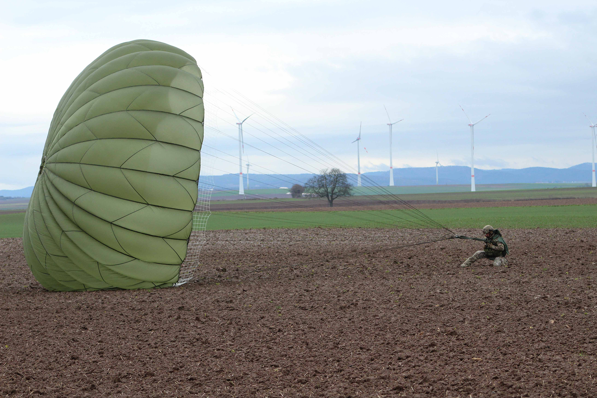 A U.S. Army paratrooper lands at Alzey drop zone Dec. 18, 2019, after jumping off a C-160 during Operation Toy Drop 2019, at Alzey, Germany. (Staff Sgt. Sinthia Rosario/Army)