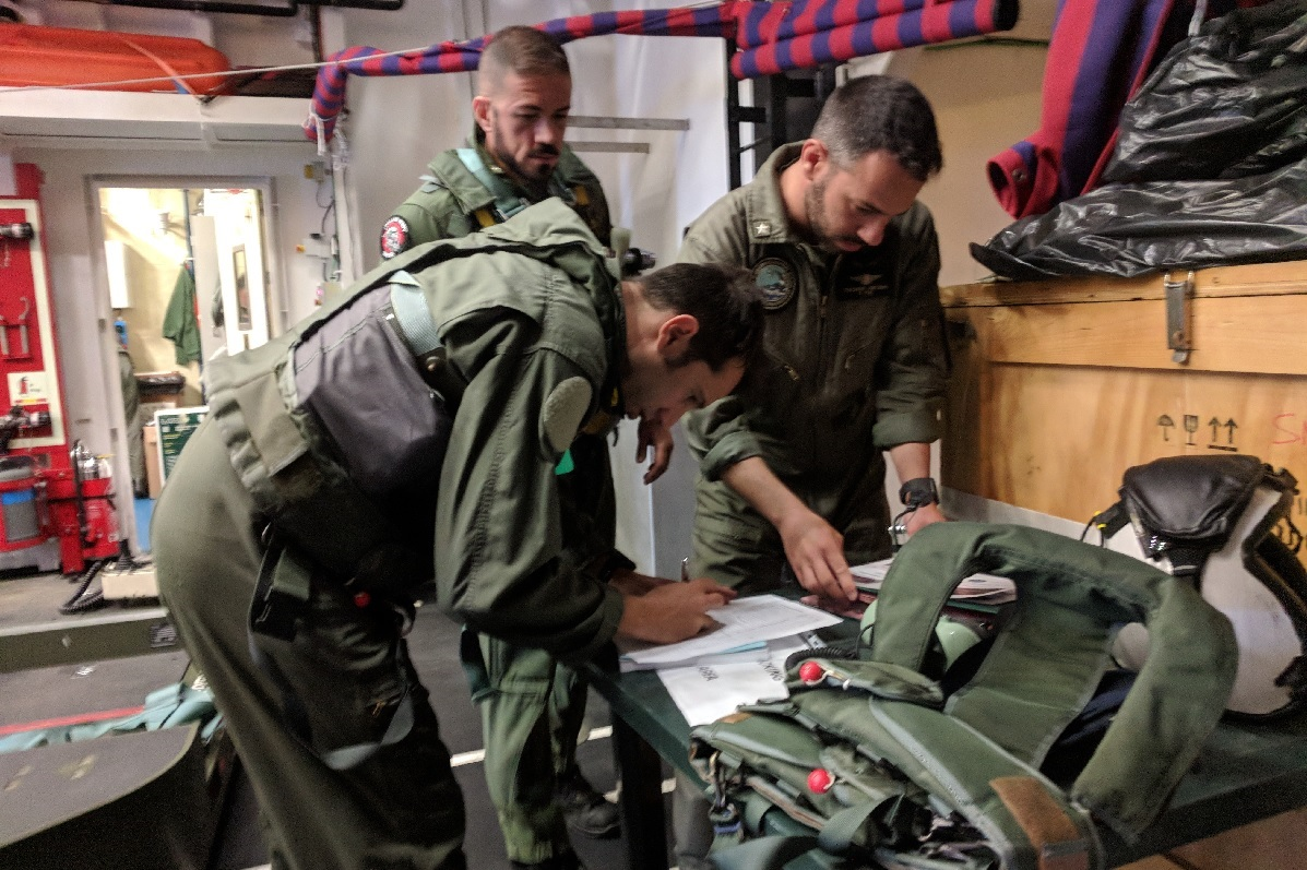 The Italian FREMM Alpino's air boss reviews the preflight checklist, with the aircrew looking on. (David B. Larter/Staff)