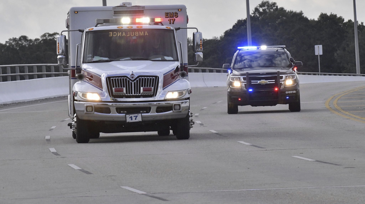 Police cars escort an ambulance after a shooter opened fire inside Naval Air Station Pensacola on Friday. (Tony Giberson/ Pensacola News Journal via AP)