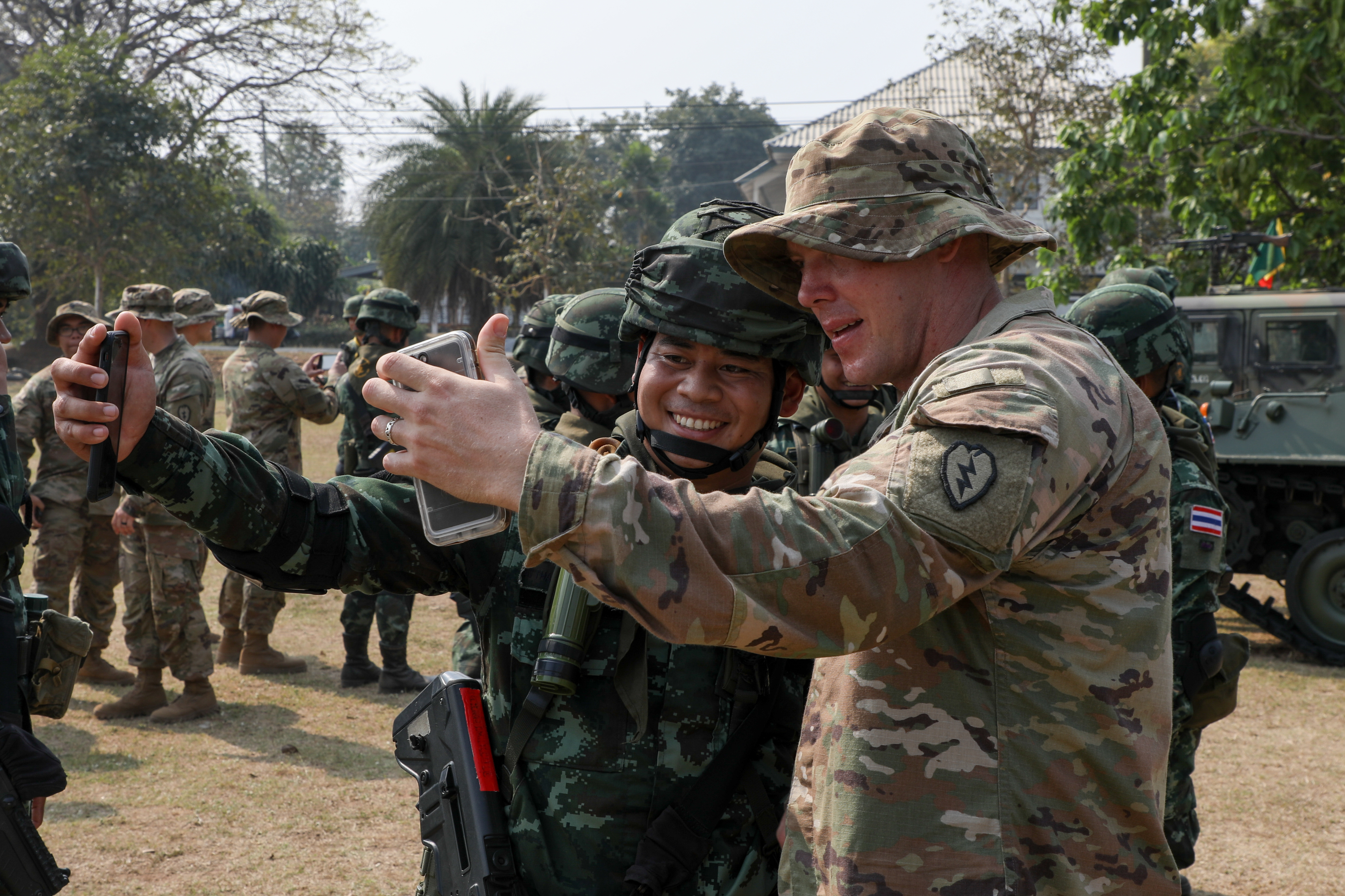 U.S. Army Sgt. William J. Cosgrove and Royal Thai Armed Forces Sgt. Maj. 3 Attaporn Uttarahong take a photo together during a break at the rehearsal for the Exercise Cobra Gold 18 opening ceremony on Camp Friendship, Thailand, Feb. 9, 2018. (Staff Sgt. David N. Beckstrom/Army)
