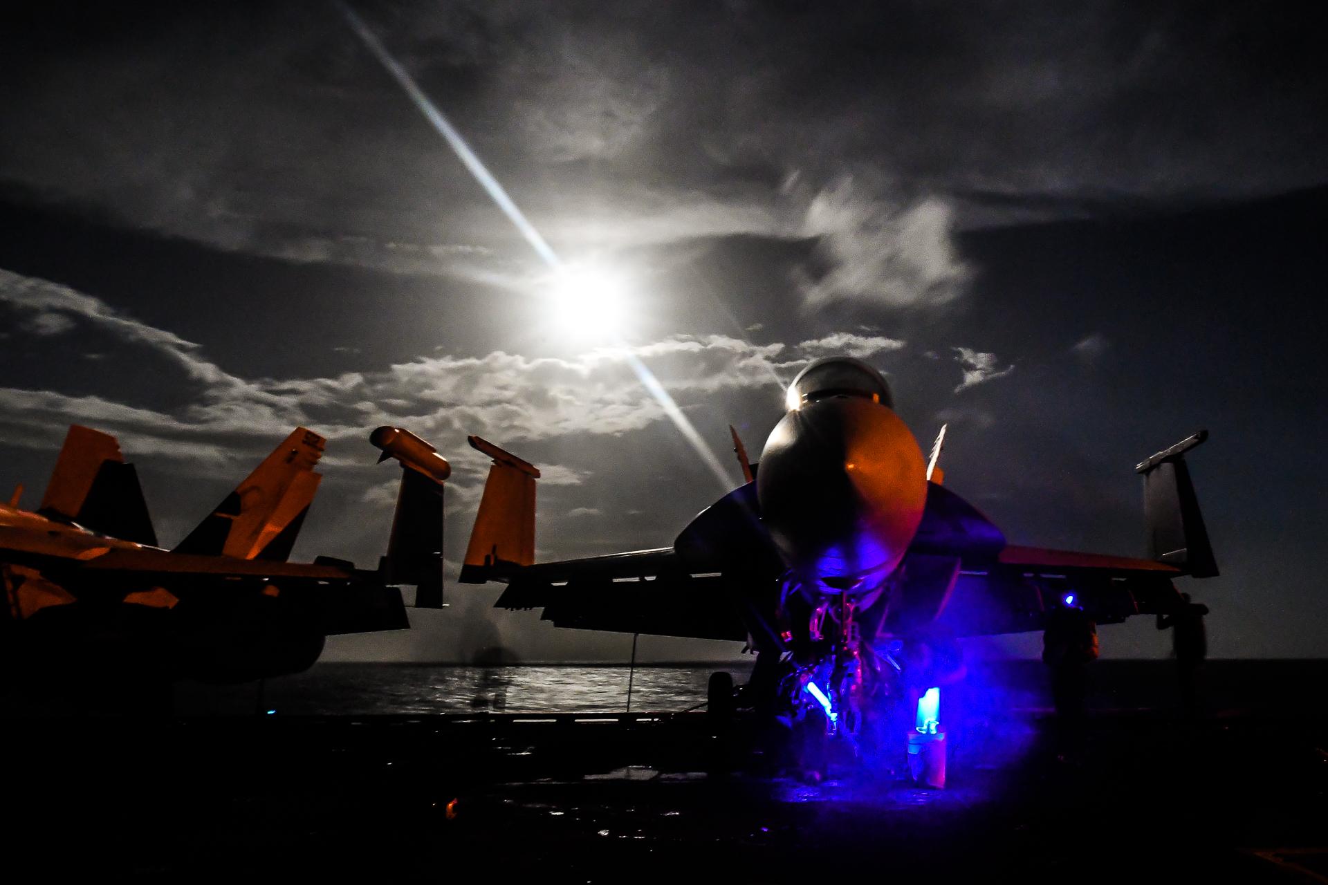 Sailors inspect the landing gear of an F/A-18F Super Hornet, assigned to the