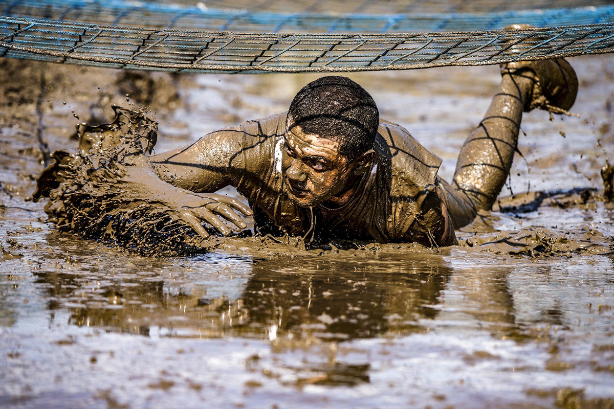 A participant of the 7th annual Rugged Terrain Obstacle Run low crawls through mud April 6, 2019, in the Grafenwoehr Training Area, Germany. (Sgt. Christopher Stewart/Army)
