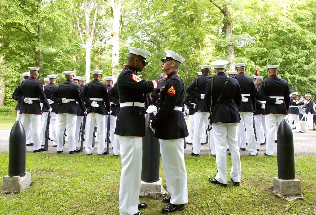 A U.S. Marine , left, helps another Marine adjust his tunic as they participate in a commemoration at the American Marine Memorial in Belleau Wood prior to a service at the Aisne-Marne American Cemetery in Belleau, France, Sunday, May 27, 2018. (Virginia Mayo/AP)