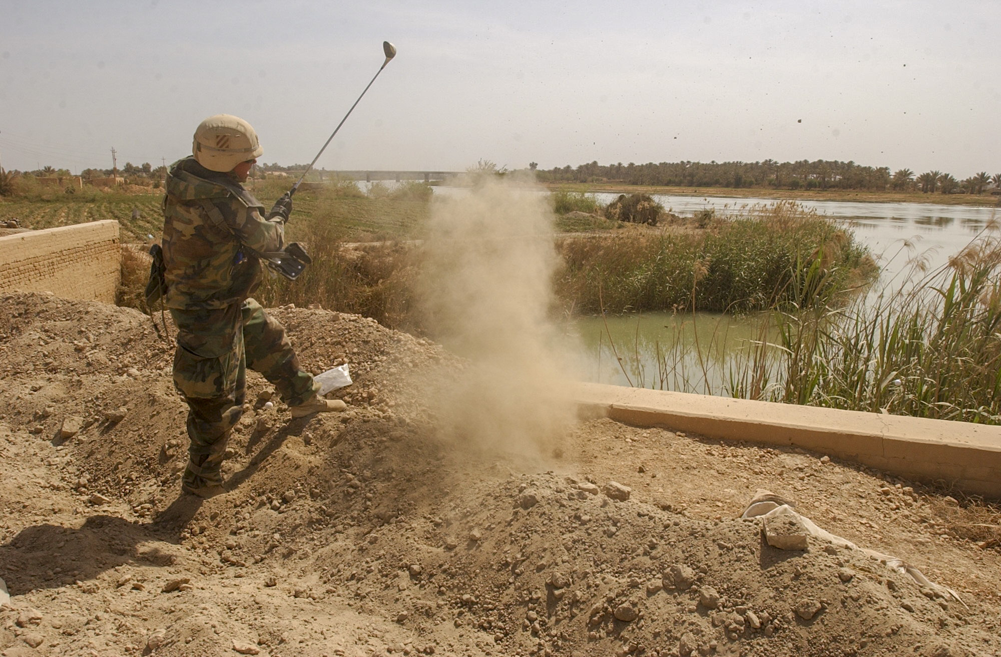 Major Brad Gavle, 39 from Decorah, Iowa of the 3rd Squadron, 7th Cavalry Regiment takes a moment during a pause in combat to hit a golf ball into the Euphrates River on April 3, 2003, 20km south of Baghdad, Iraq. A major assault was launched last night by the 3rd Infantry Division as the division makes it way towards Baghdad. (Warren Zinn/Army Times)