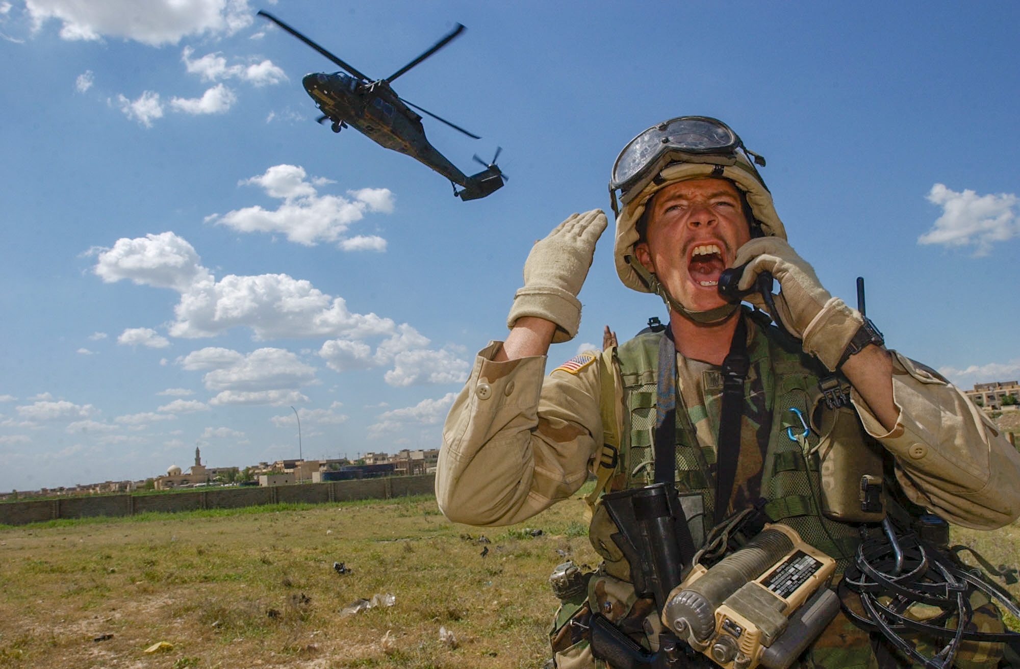 Sgt. Daniel Wiser, 25, of Waukesha, WI,yells to his section to haul ass back to the landing zone as he talks to the Blackhawk pilots before reboarding the plane as soldiers inspect vehicles in Mosul Wednesday, 4/30/03. The headquarters mortars, 3rd Battalion, 502nd Infantry Regiment, 101st Airborne Division (Air Assault) section is using the UH-60 Blackhawk helicopter to conduct searches to locate and shut down black market activity in the third largest city in Iraq. (Rob Curtis/Army Times)
