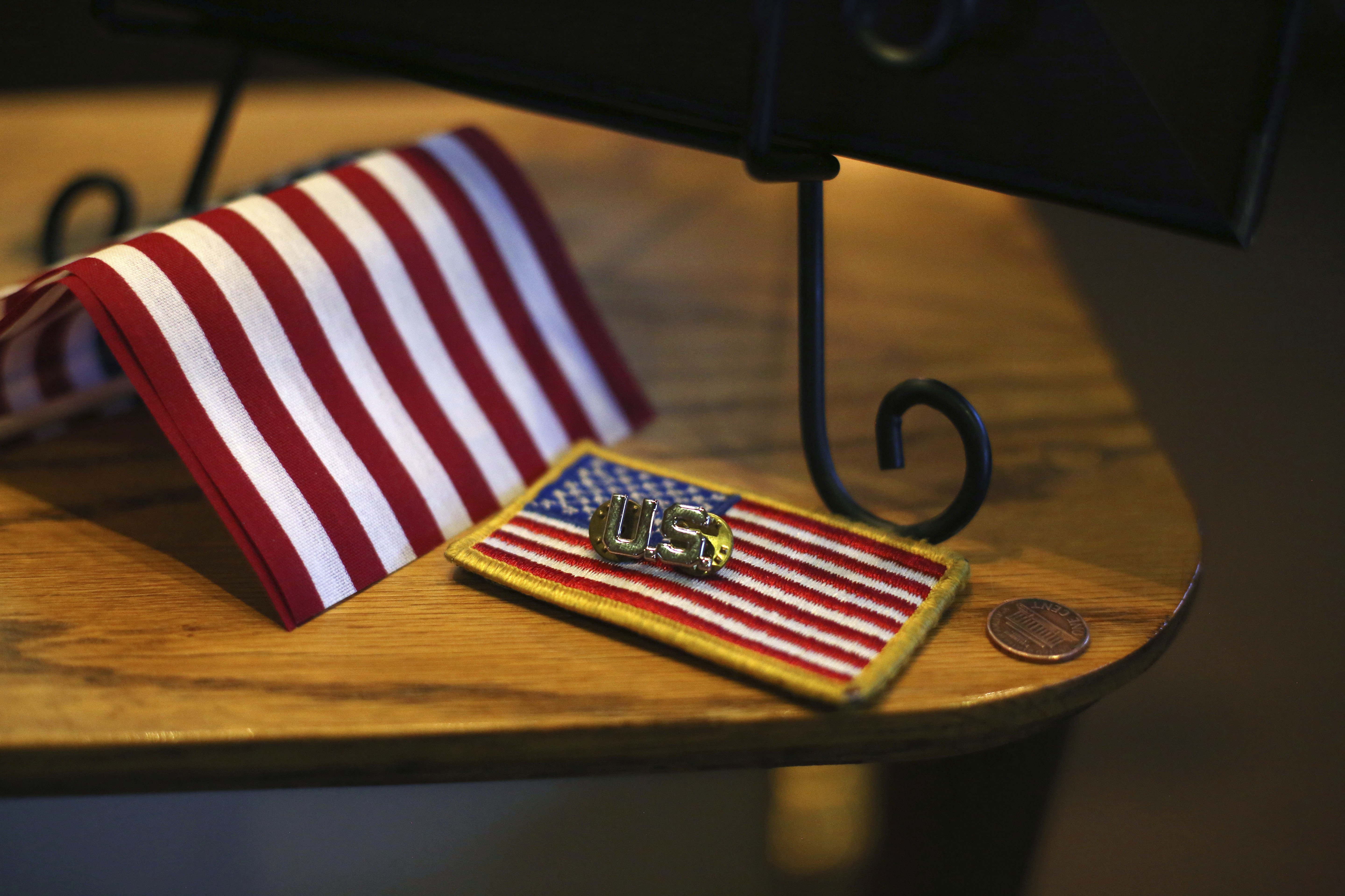 Pins, patches, flags and pennies are left on a pedestal honoring WWII Marine veteran Cpl. Remigio