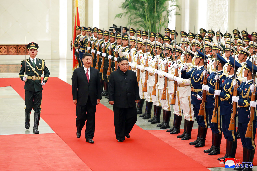 In this June 19, 2018, photo provided on June 20, 2018, by the North Korean government, Chinese President Xi Jinping, center left, and North Korean leader Kim Jong Un, center right, inspect the honor guard at the Great Hall of the People in Beijing, China. (Korean Central News Agency/Korea News Service via AP)