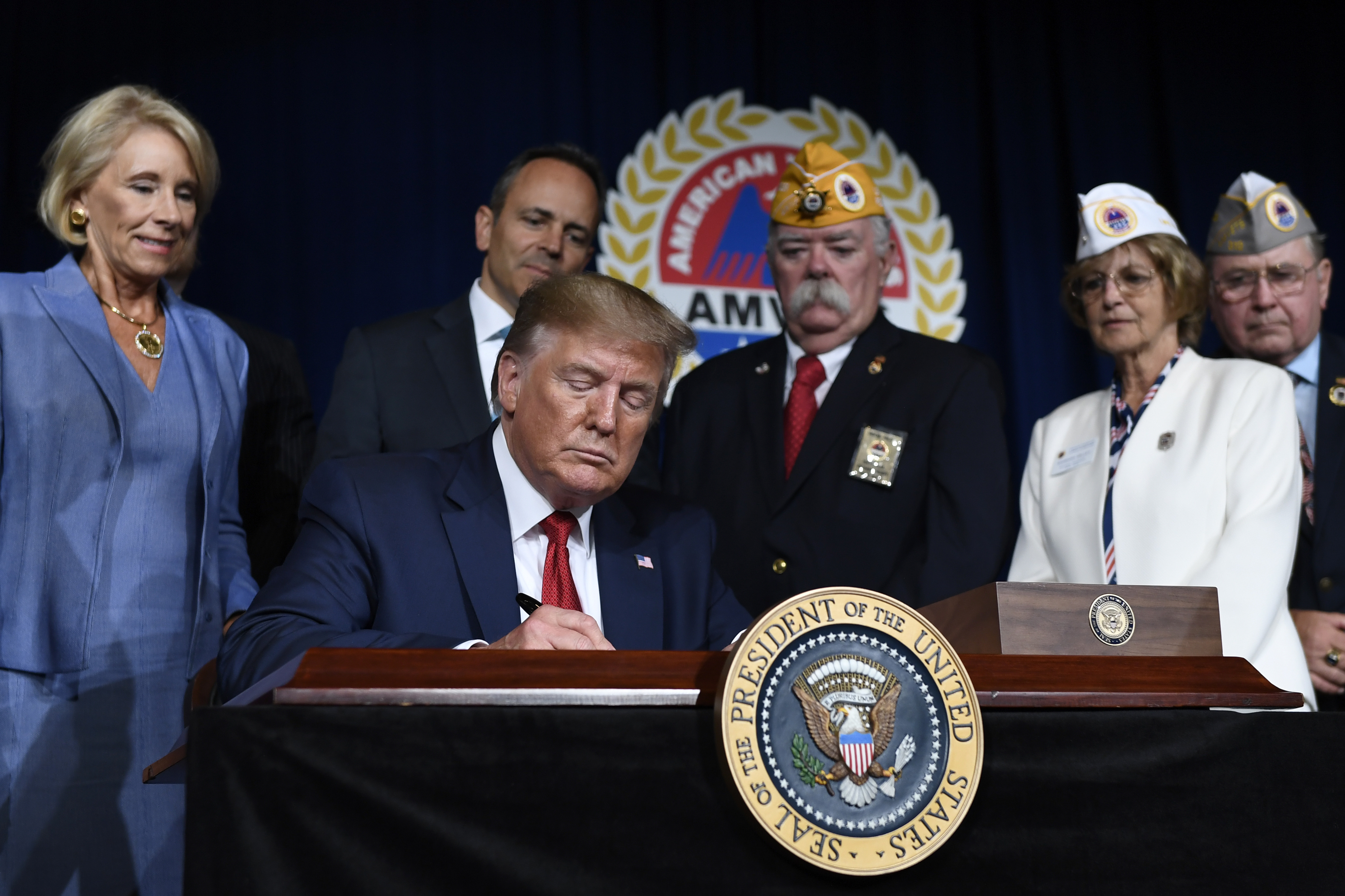 President Donald Trump signs a memorandum on veterans' student loan debt following his speech at the AMVETS 75th National Convention in Louisville, Ky., on Aug. 21, 2019. (Susan Walsh/AP)