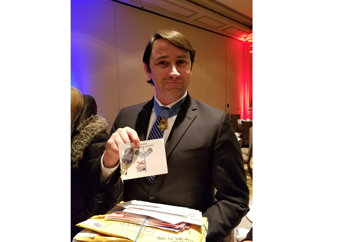 Wililam Swenson poses with some of the mail he received during a Medal of Honor luncheon March 22. Swenson earned the Medal of Honor for his actions in Afghanistan in 2009, helping fend off an enemy ambush and making multiple trips into a