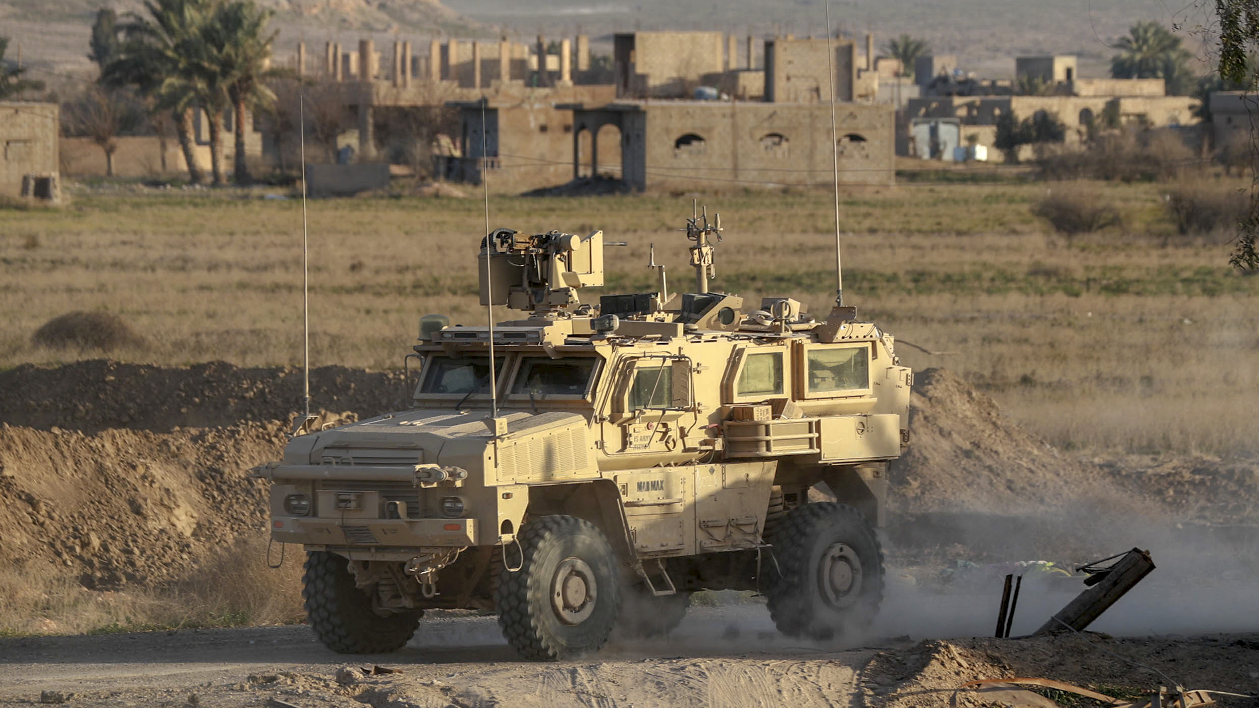 A US military vehicle drives through the Syrian village of Baghuz in the countryside of the eastern Deir Ezzor province on January 26, 2019. - The Syrian Democratic Forces (SDF), with backing from a US-led coalition, are battling to expel the last jihadists of the Islamic State group from hamlets in the eastern province of Deir Ezzor. (DELIL SOULEIMAN/AFP/Getty Images)