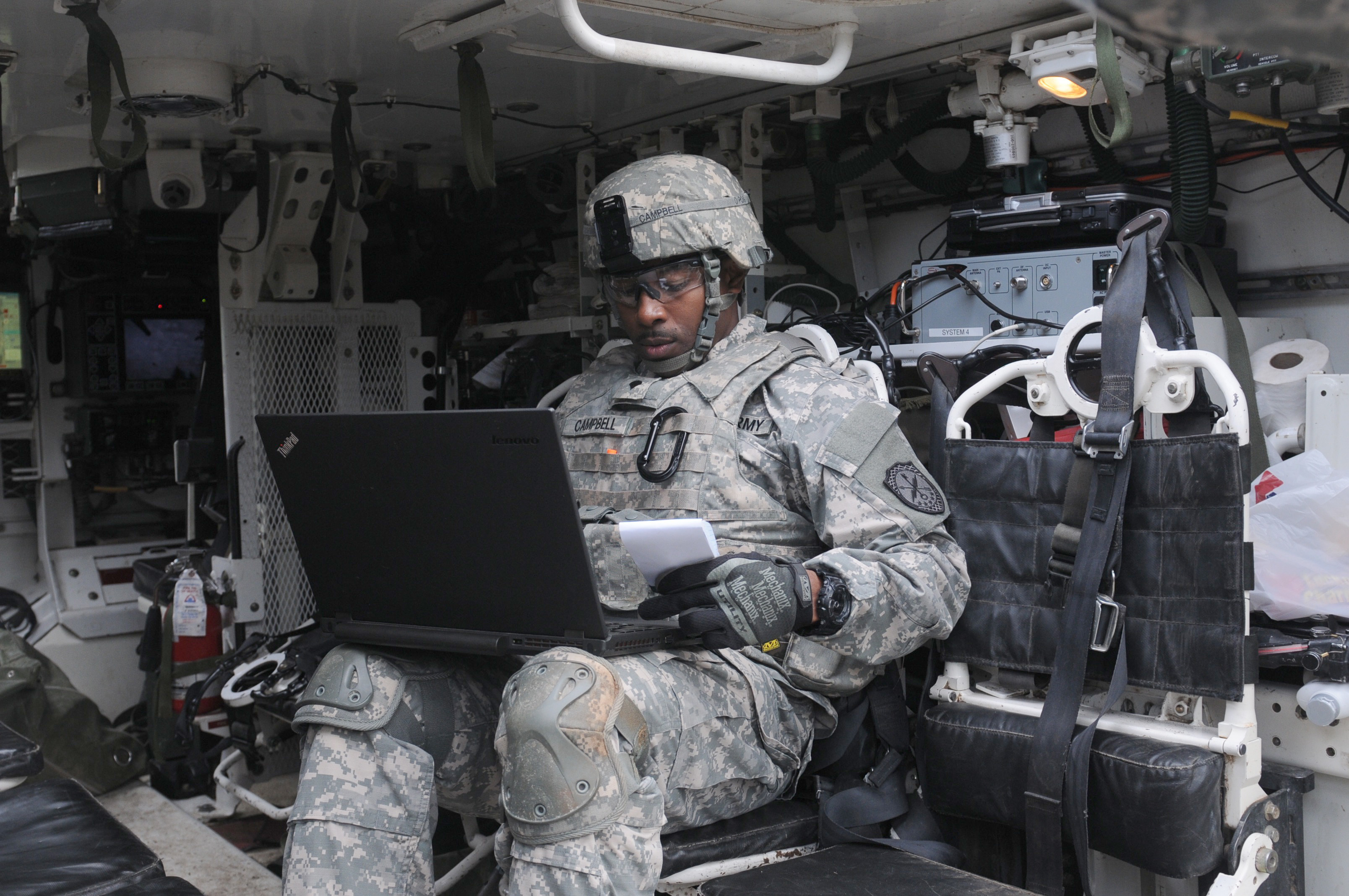 A Cyber Soldier assigned to the 780th Military Intelligence Brigade prepares his equipment inside a Stryker vehicle during an integrated cyber exercise at Joint Base Lewis-McChord (Capt. Meredith Mathis/Army).