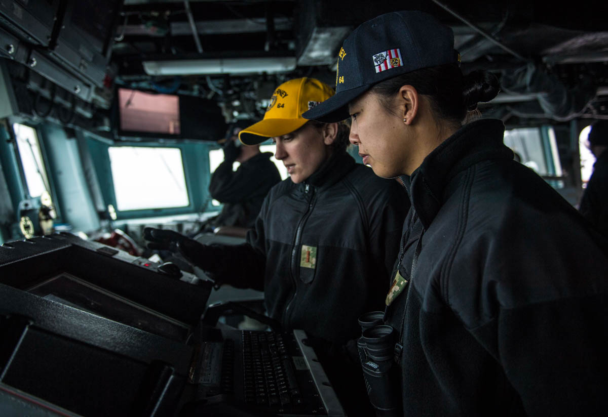Ensigns Karyn Lee, left, and Michelle Nelson look at the voyage maintenance system while standing watch aboard the guided-missile destroyer Carney. (MC2 James R. Turner/Navy)
