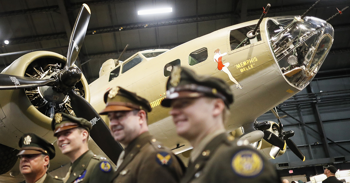 Visitors and period re-enactors gather beside the Memphis Belle, a Boeing B-17
