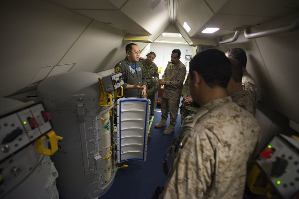 Lt. Fan Yang, left, formerly a tactical coordinator assigned to Patrol Squadron 5, demonstrates the systems on board a P-8A Poseidon aircraft to members of the Royal Saudi Naval Forces on March 1, 2018. (Mass Communication Specialist 2nd Class Jakoeb Vandahlen/Navy)