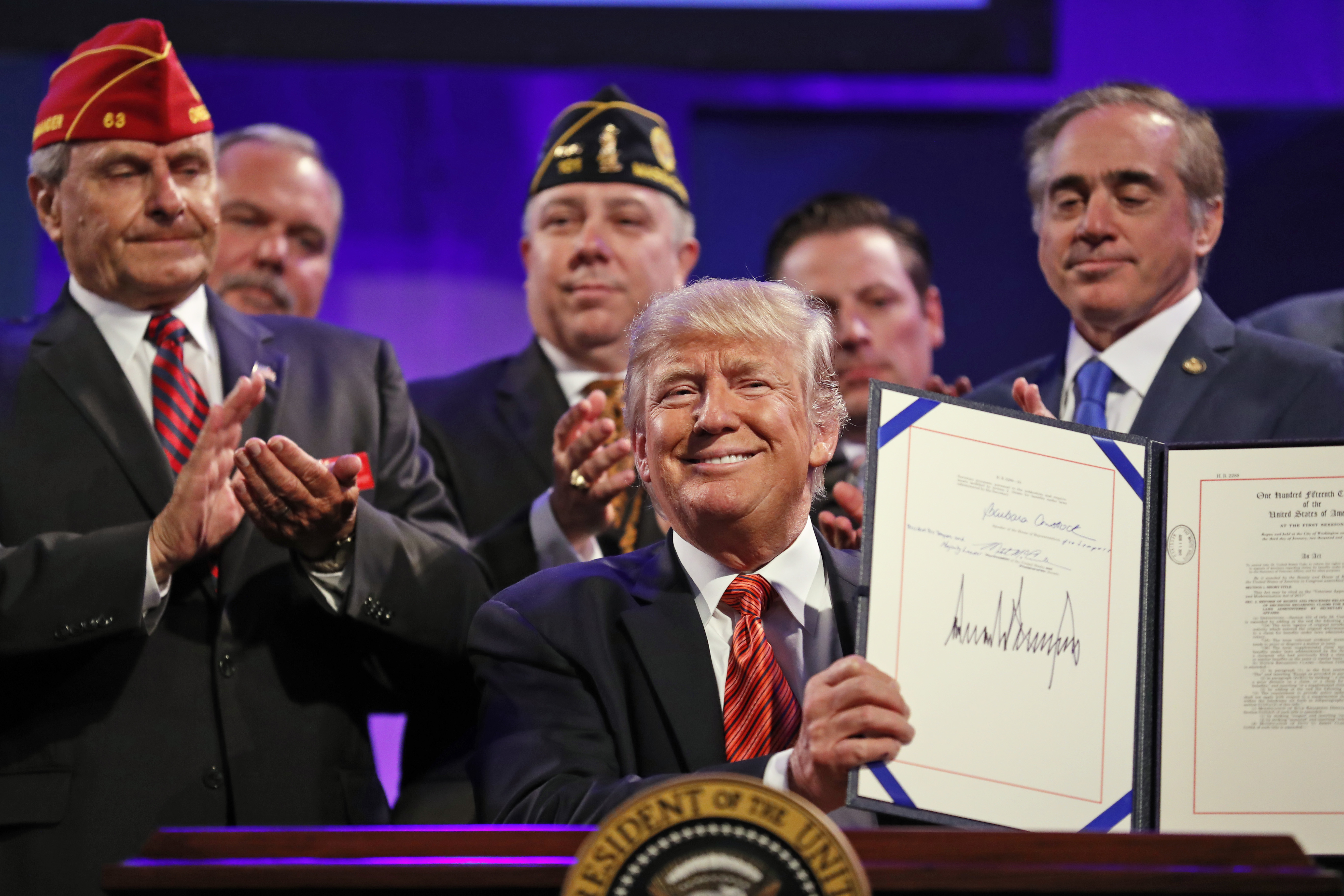 President Donald Trump holds up a signed Veterans Appeals Improvement and Modernization Act on Aug. 23, 2017, at the National Convention of the American Legion in Reno, Nev. (Alex Brandon/AP)