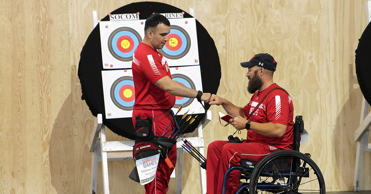 Team Marine Corps Lance Cpl. Matthew Maddux, left, fist bumps, Gunnery Sgt. Douglas Goddfrey during the 2018 DoD Warrior Games archery competition at the Air Force Academy in Colorado Springs, Colo. June 7, 2018. (EJ Hersom/DoD)