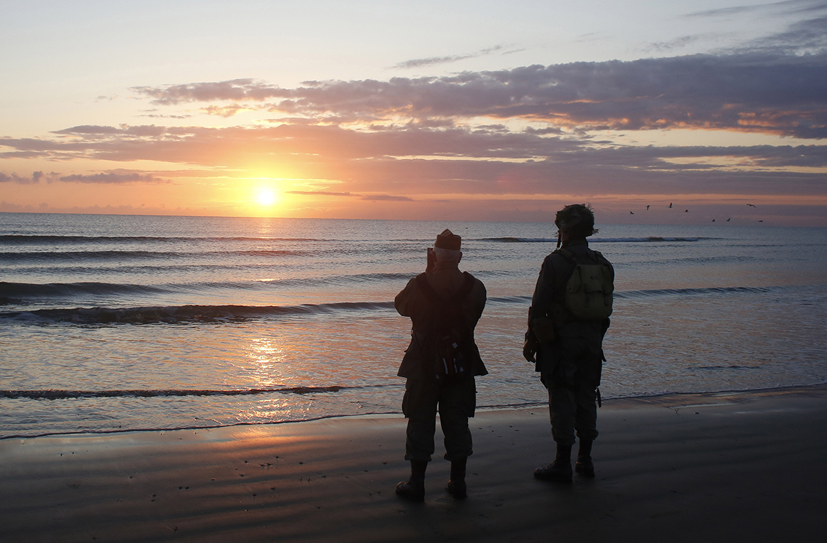 World War II re-enactors stand looking out to sea on Omaha Beach in Normandy, France, at dawn on Thursday, June 6, 2019 during commemorations of the 75th anniversary of D-Day. (Thibault Camus/AP)