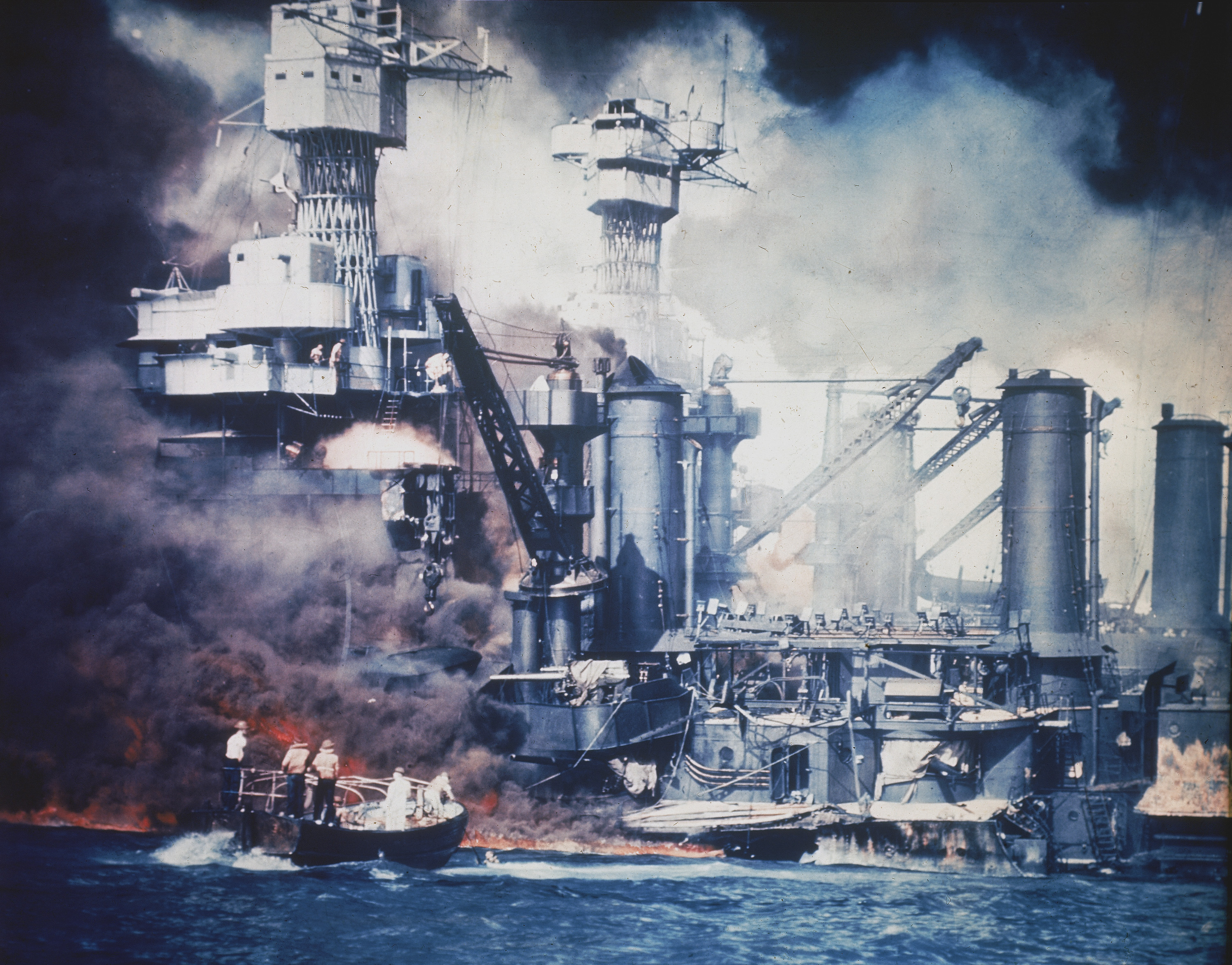 A small boat rescues a USS West Virginia crew member from the water after the Japanese bombing of Pearl Harbor, Hawaii on Dec. 7, 1941 during World War II. Two men can be seen on the superstructure, upper center. The mast of the USS Tennessee is beyond the burning West Virginia. (AP Photo)