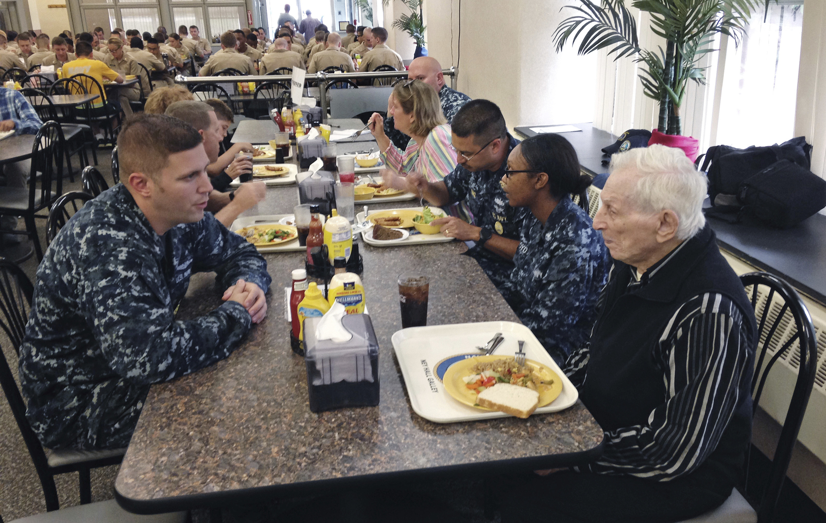 WWII veteran Edmund DelBarone, right, shares stories over lunch with Heath Cruse, left, a cook at the galley during a tour at Naval Station Newport, in Newport, R.I., Thursday July 27, 2017. DelBarone, a 96-year-old World War II veteran, once dreamed of returning to a Navy installation to reminisce about his naval career, and help of a nonprofit it has become a reality. (Jennifer McDermott/AP)