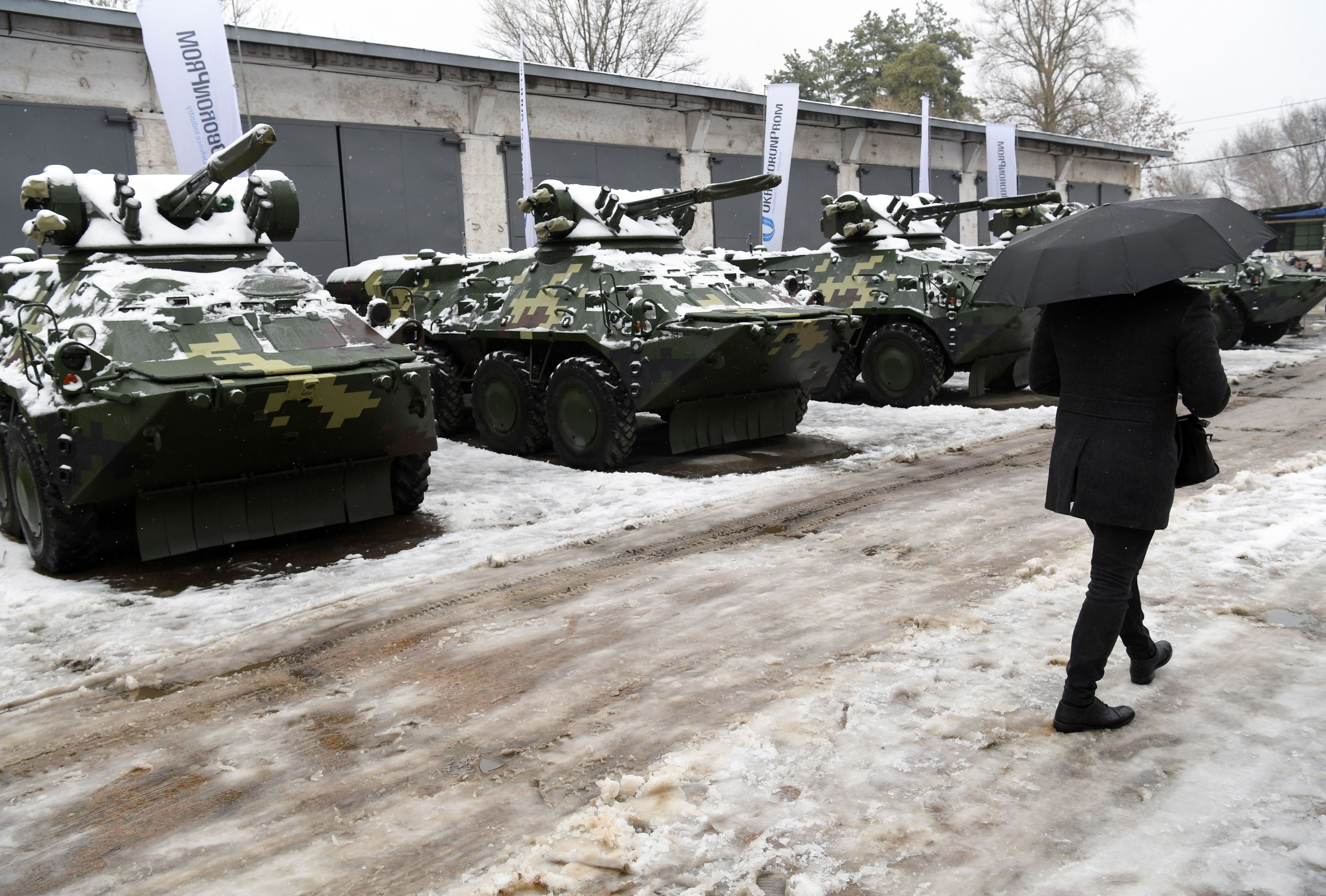A man walks in front of new armored personnel carriers in Kiev on Nov. 15, 2018, after the handover of military weapons and equipment to Ukrainian servicemen taking part in armed conflict with Russia-backed separatists in the country's Donetsk region. (Sergei Supinsky/AFP via Getty Images)