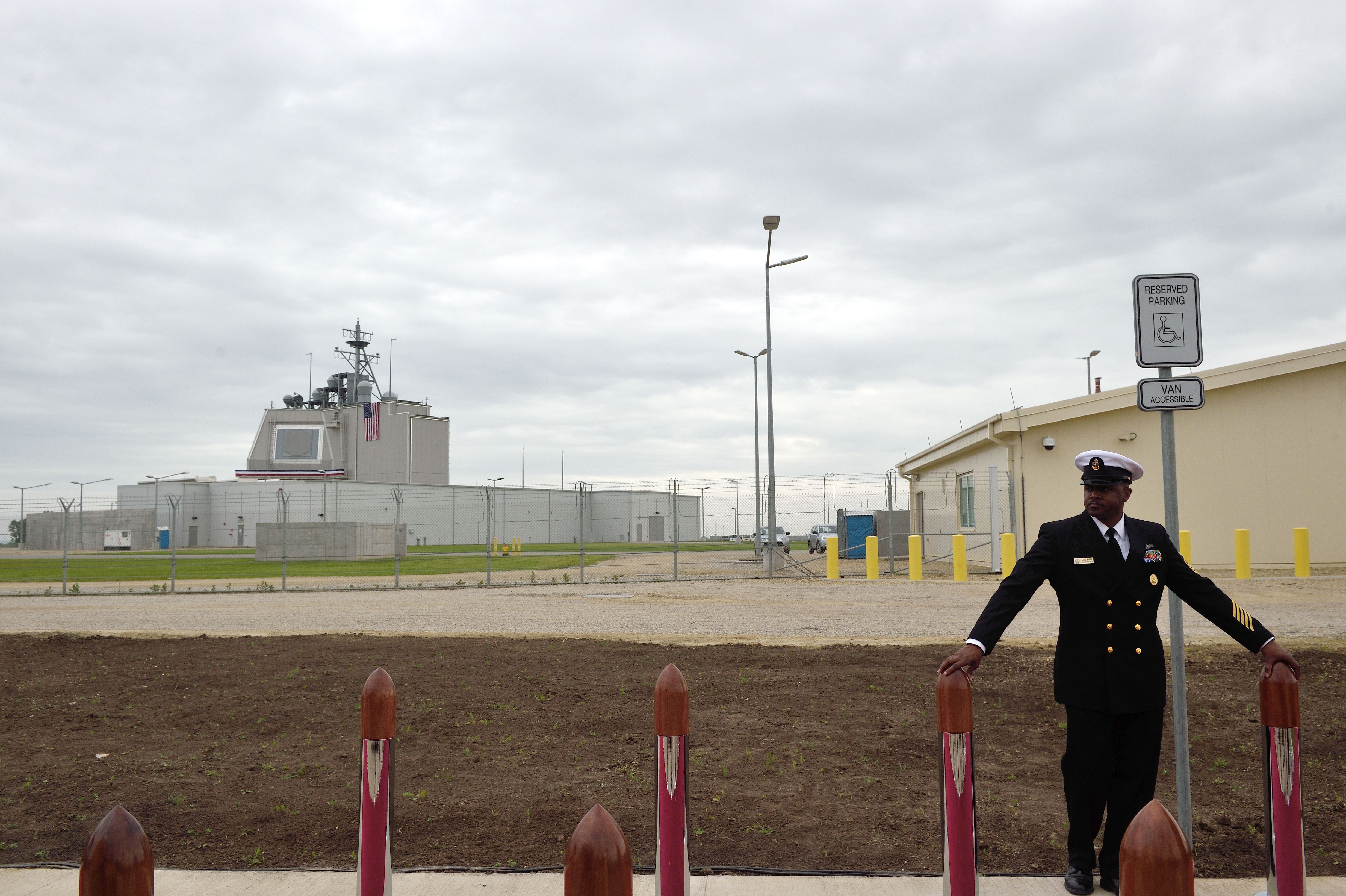 US Army personnel stands at the red carpet ahead an inauguration ceremony of the US anti-missile station Aegis Ashore Romania (in the background) at the military base in Deveselu, Romania on May 12, 2016. Poland's Aegis Ashore site continue to be plagued by construction issues and now won't be operational until possibly 2022. Aegis Ashore is a land-based capability of the Aegis Ballistic Missile Defense (BMD) System. (Photo by DANIEL MIHAILESCU/AFP/Getty Images)