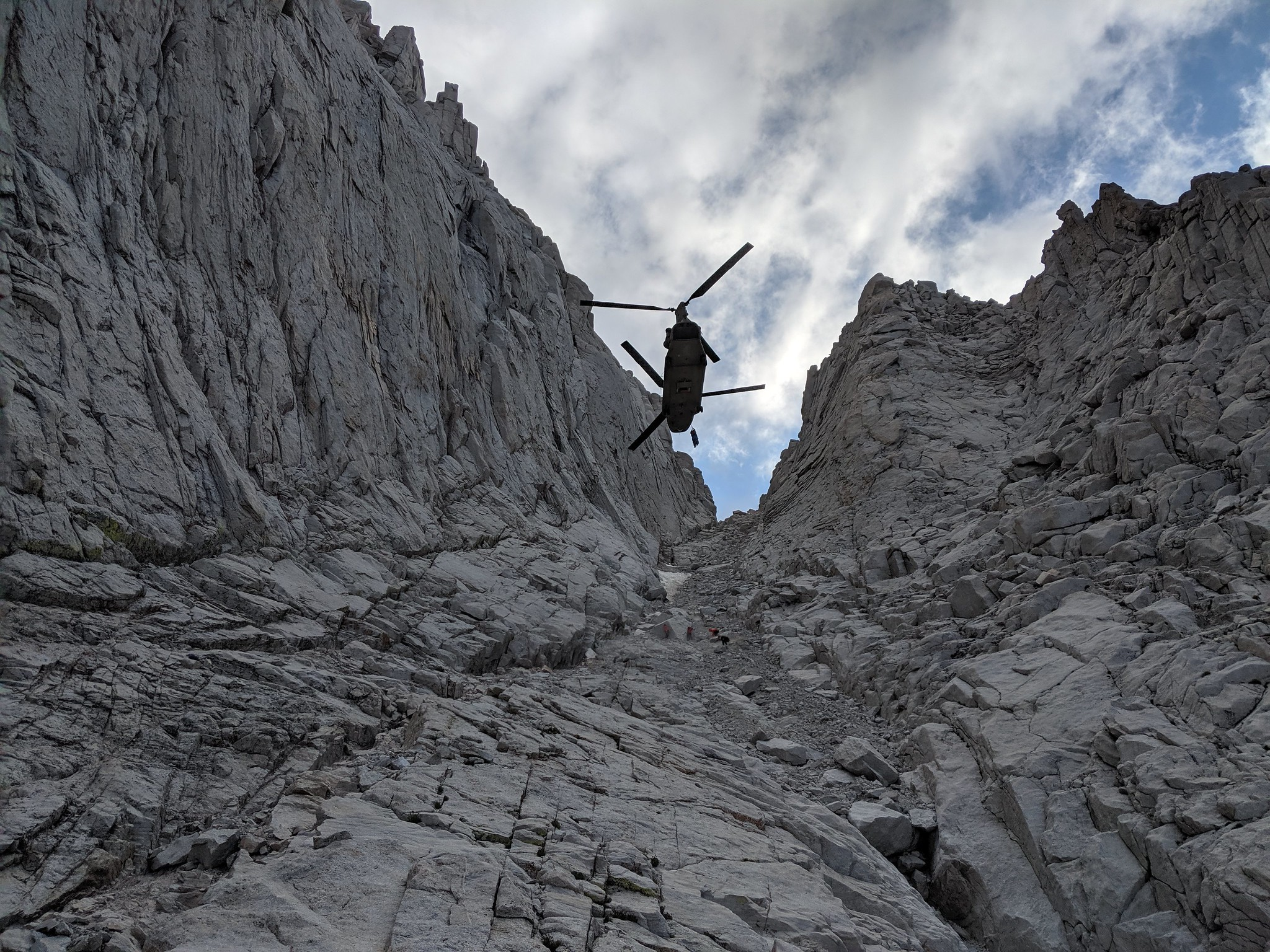 A California Army National Guard CH-47F Chinook helicopter hovers Aug. 25, 2019, as an injured hiker is hoisted on a litter from an area 13,800 feet up Mount Whitney in Inyo County, Calif. (Photo courtesy Inyo County Search and Rescue)