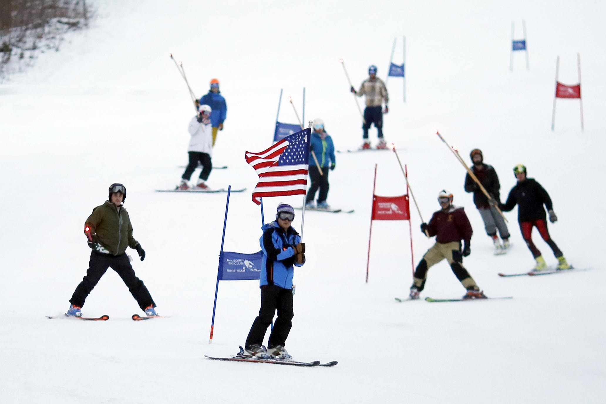 As former teammates of Navy Lt. Steven Combs ski through the gates in total silence, the only sound the crowd gathered below could hear was the swishing of skis through snow on Wednesday, Feb. 14, 2018. The former racers, coaches, friends, and family of the late Lt. Combs, along with current high school ski racers, gathered at Bousquet Ski Area in Pittsfield to pay tribute to the navy pilot who was killed in a crash on the Philippine Sea on Nov. 22, 2017. (Stephanie Zollshan/The Berkshire Eagle via AP)