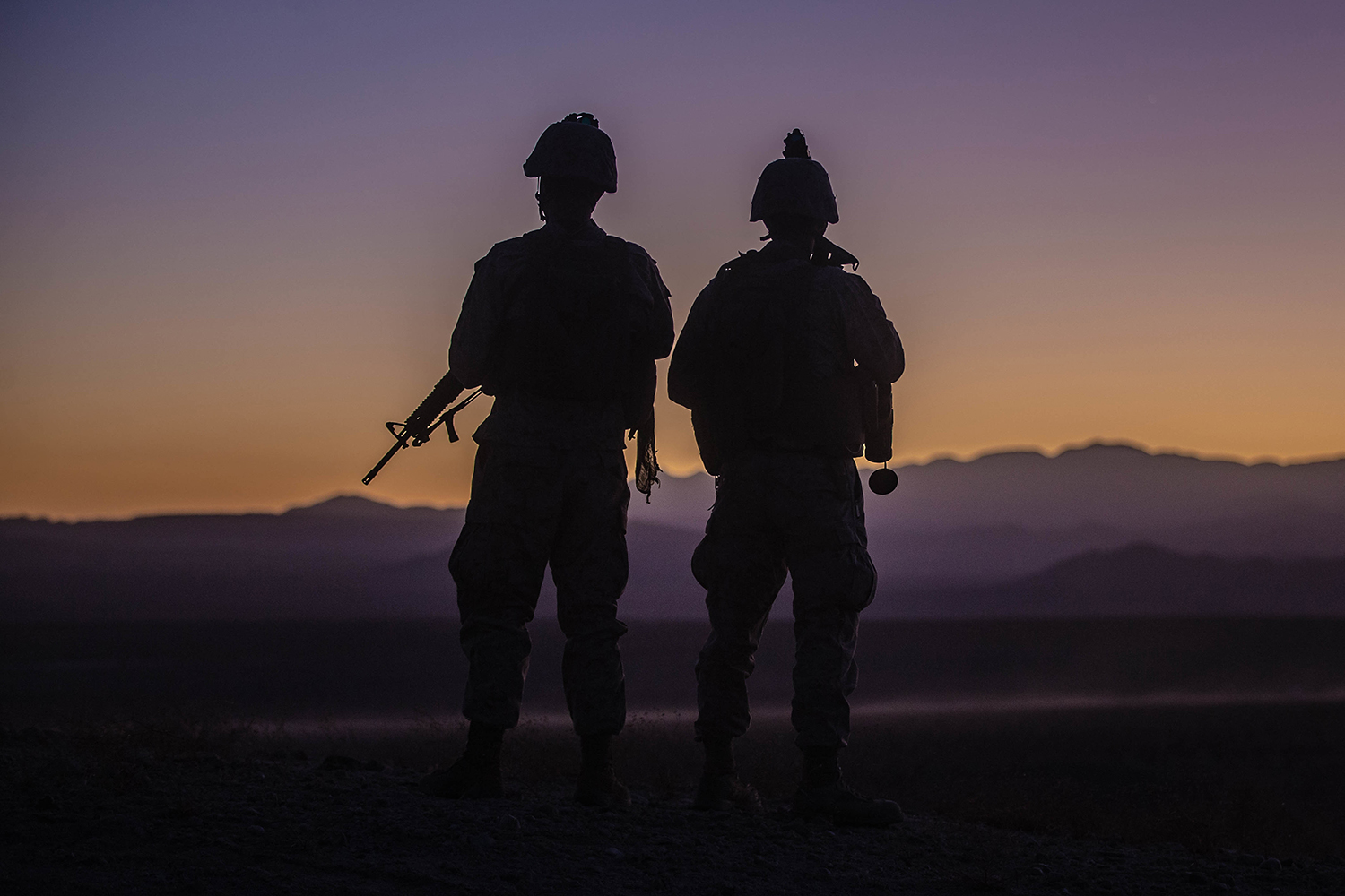 Marine Corps Staff Sgt. William Huffman, left and Cpl. Stephen Gibbons prepare to depart an observation point during Integrated Training Exercise (ITX) 1-20 at Marine Air Ground Combat Center Twentynine Palms, Calif., Oct. 28, 2019. (Cpl. Scott Jenkins/Marine Corps)