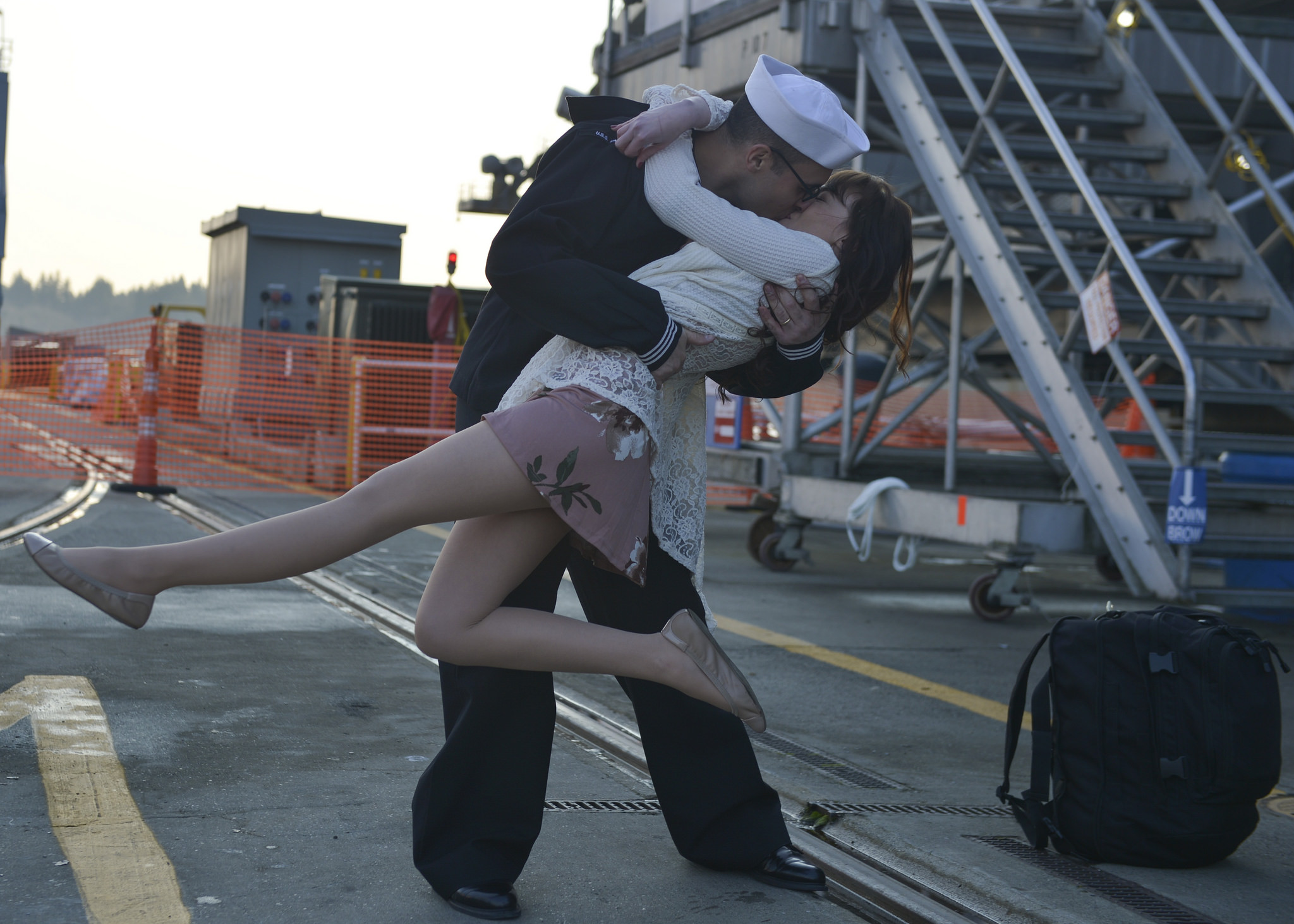 U.S. Navy Logistics Specialist 3rd Class Michael Zegarra, assigned to the aircraft carrier USS Nimitz (CVN 68), kisses his wife on the pier during the ship's homecoming in Bremerton, Wash, Dec. 10, 2017. The Nimitz Carrier Strike Group is returning from a regularly scheduled deployment from the Indo-Asia-Pacific region and Arabian Gulf. (MC3 Ian Kinkead/Navy)