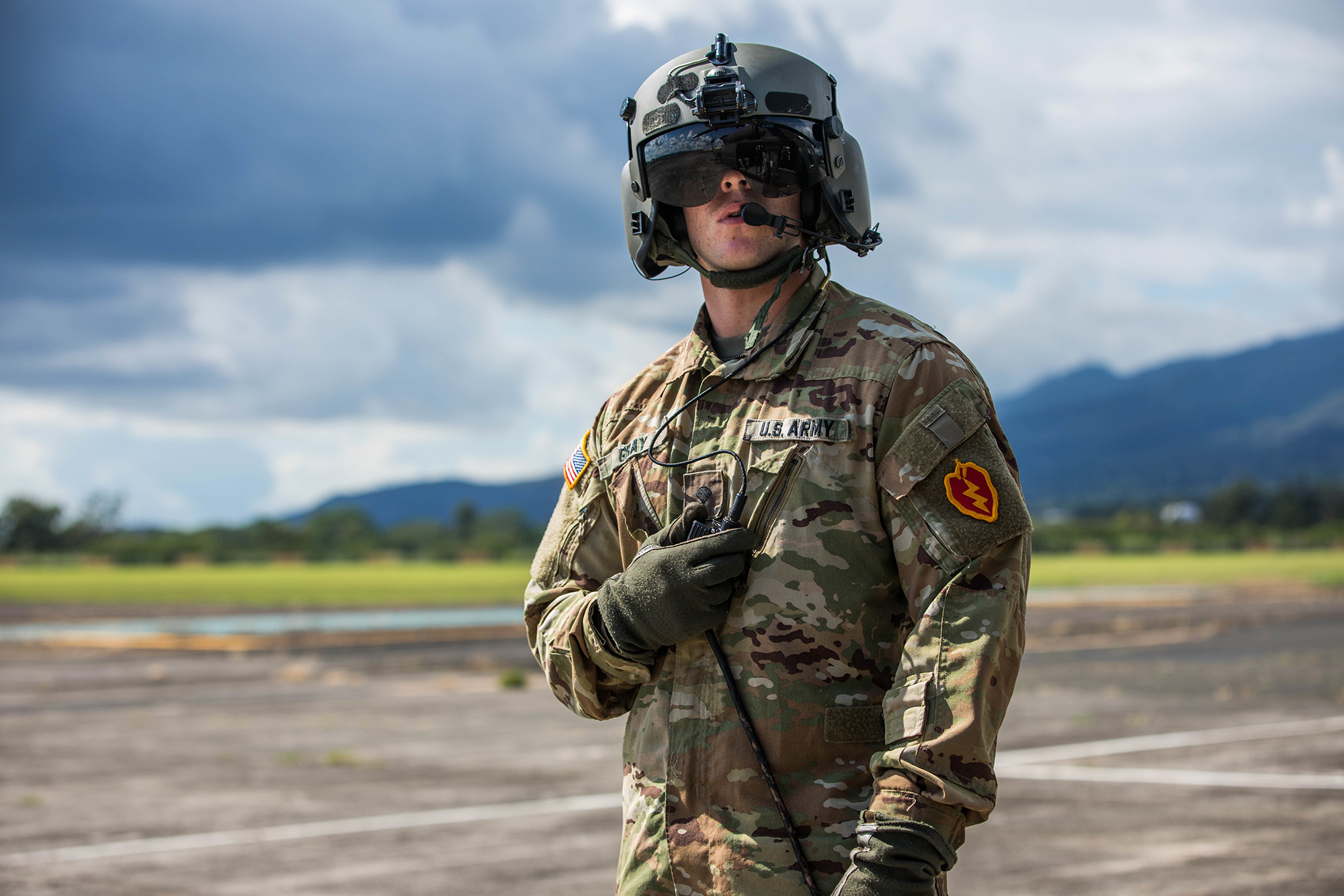 Spc. Jon Gray, a crew chief with 25th Combat Aviation Brigade, gets ready for the official review of the 25th Infantry Division's soldiers, complete with flyover from 25th CAB helicopters Oct. 31, 2019, at Schofield Barracks, Hawaii. Soldiers wear the 25th Infantry Divisions colored patch during Tropic Lightning Week which is the first time it is displayed with the OCP uniform. (Sgt. Sarah D. Sangster/Army)