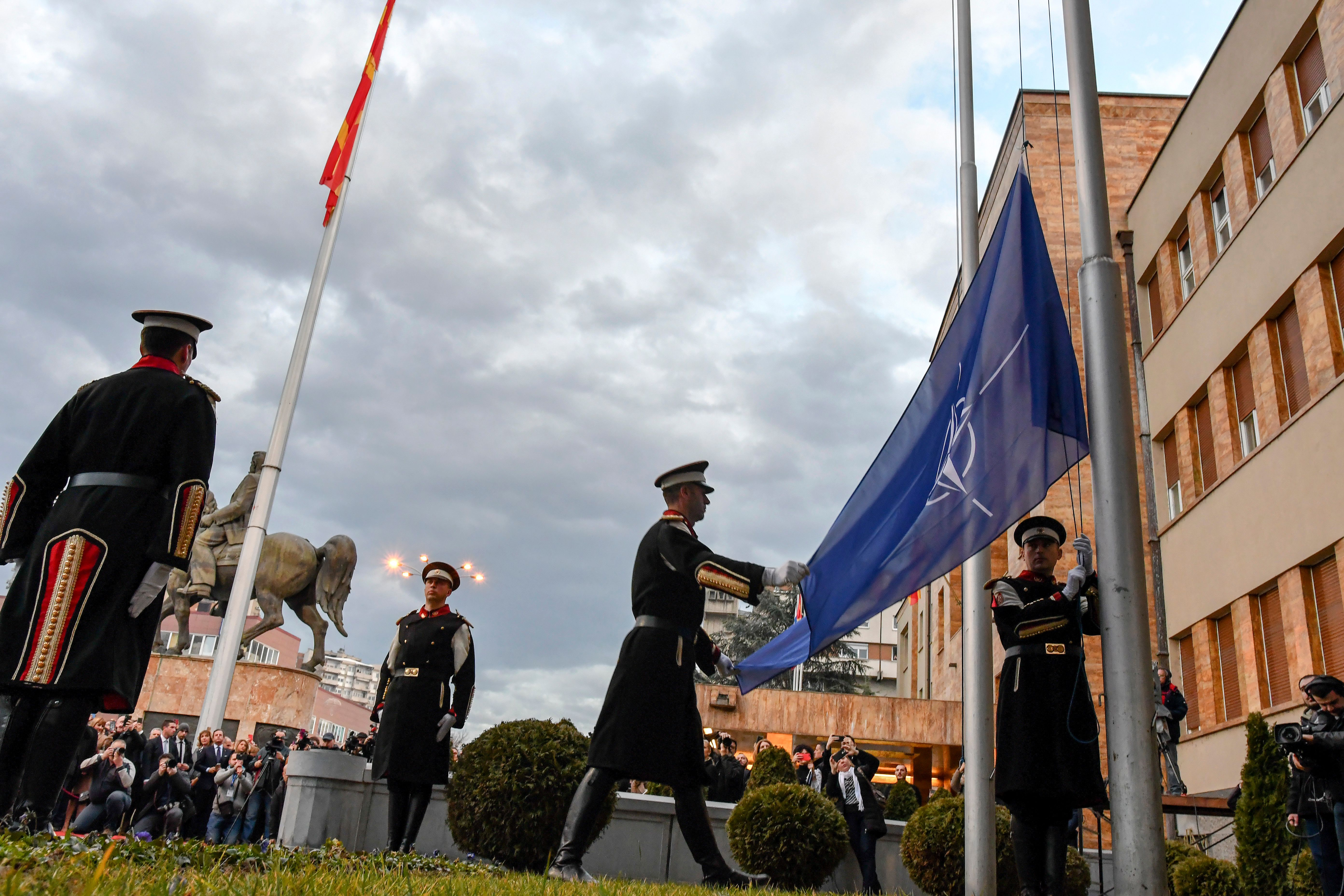 Honor guard members raise the NATO flag during a ceremony in front of the parliament building in Skopje, North Macedonia, on Feb. 11, 2020, after the lawmakers ratified the NATO accession agreement. (Robert Atanasovski/AFP via Getty Images)